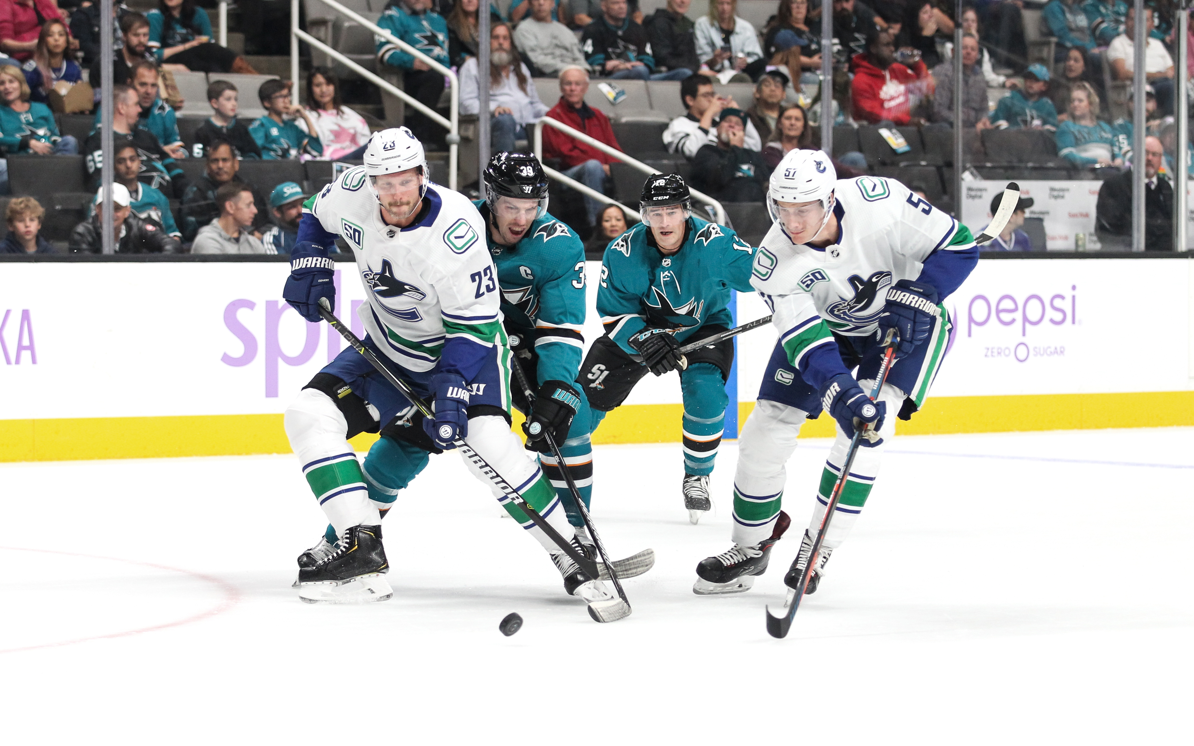 Logan Couture #39 of the San Jose Sharks battles for the puck against Alexander Edler #23 of the Vancouver Canucks at SAP Center on November 2, 2019 in San Jose, California