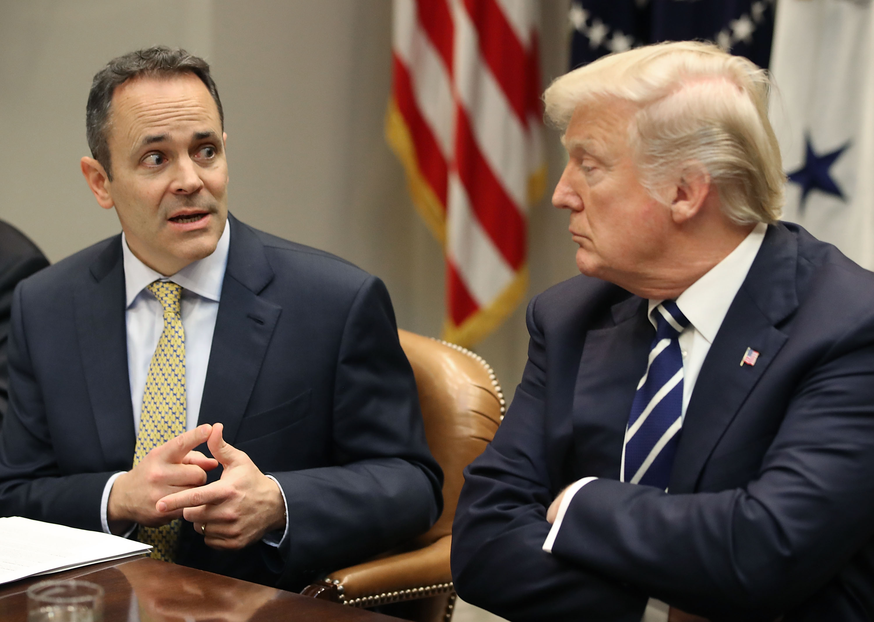 Kentucky Gov. Matt Bevin sits to the left of President Donald Trump and speaks to him at a roundtable discussion.