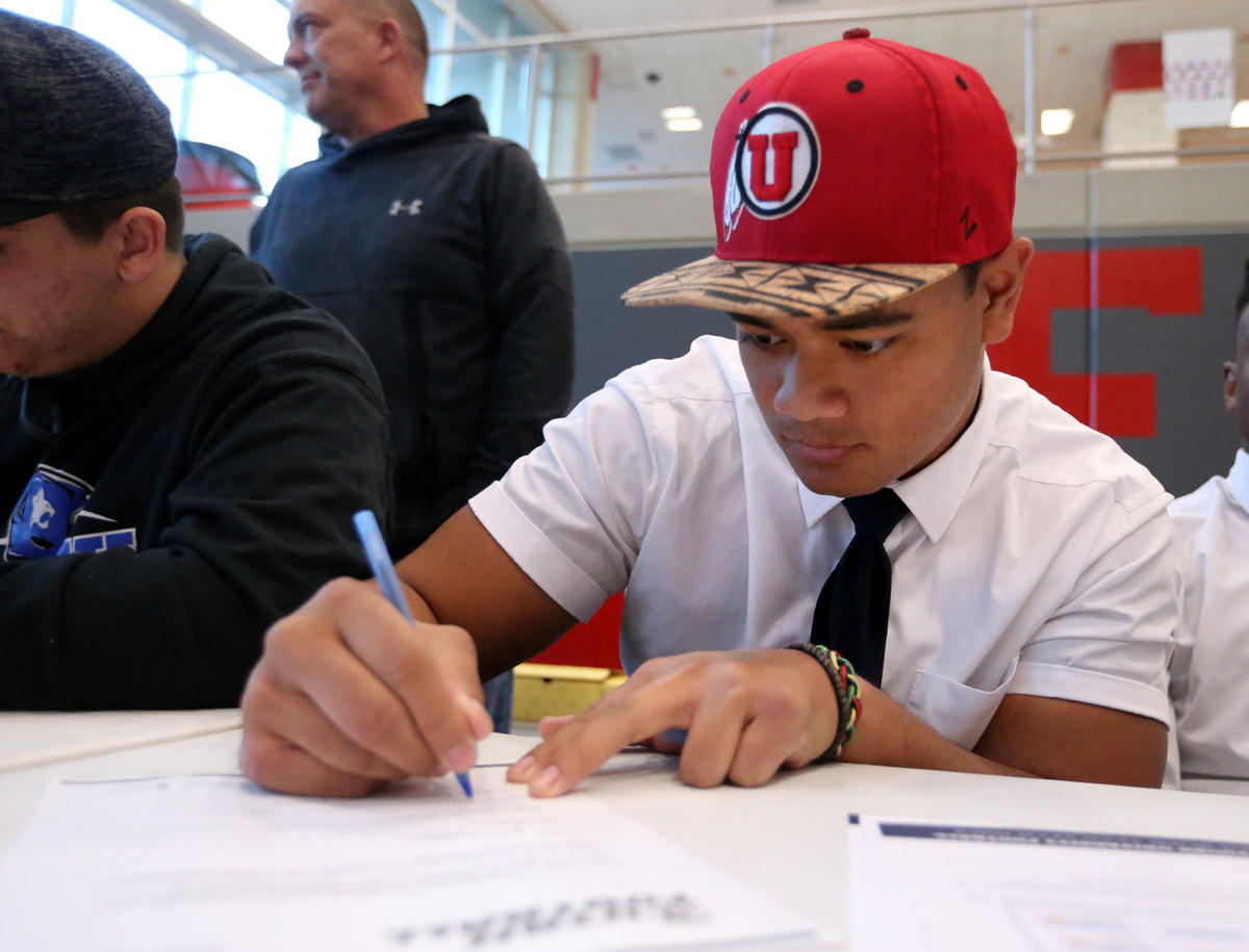Tennessee Pututau signs his letter of intent to attend the University of Utah during Signing Day at East High School in Salt Lake City on Wednesday, Feb. 7, 2018.
