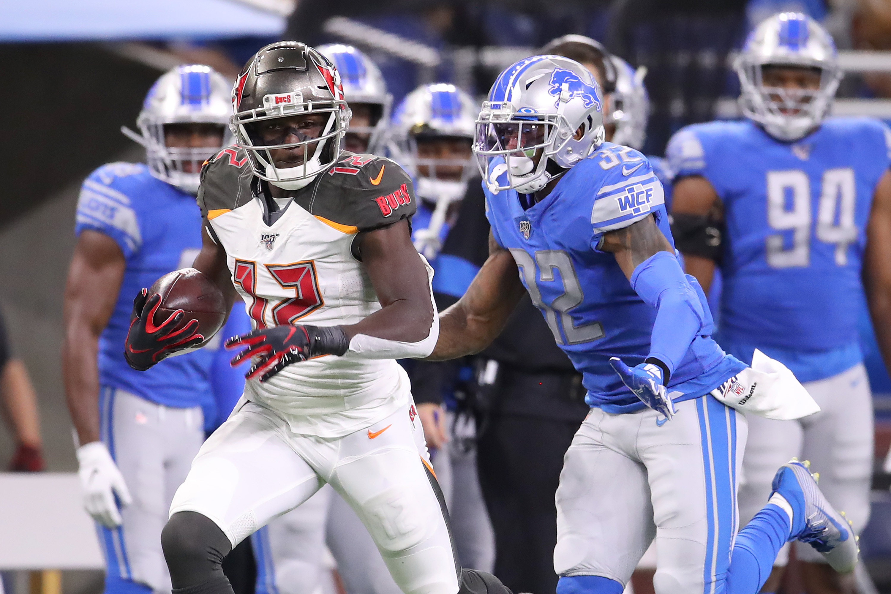 Chris Godwin of the Tampa Bay Buccaneers looks for yards after a first half catch next to Tavon Wilson of the Detroit Lions at Ford Field on December 15, 2019 in Detroit, Michigan.