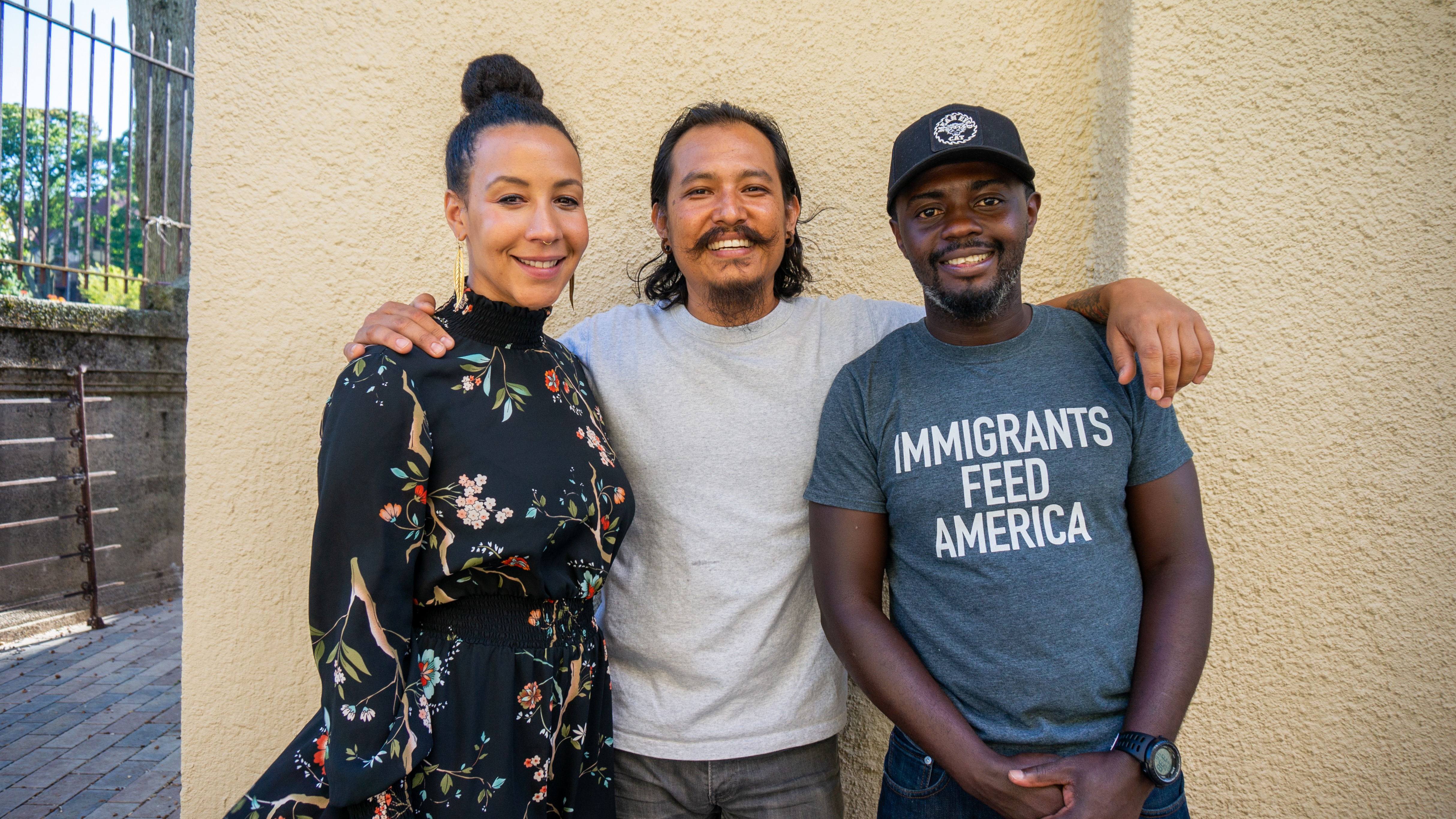 """A woman and two men stand in a line against a pale yellow cement wall outside, smiling and looking at the camera. The man in the middle has an arm around the shoulder of each person to the side. The woman on the left wears a black dress with a floral print, and the man on the right has a blue t-shirt that reads """"Immigrants feed America."""""""