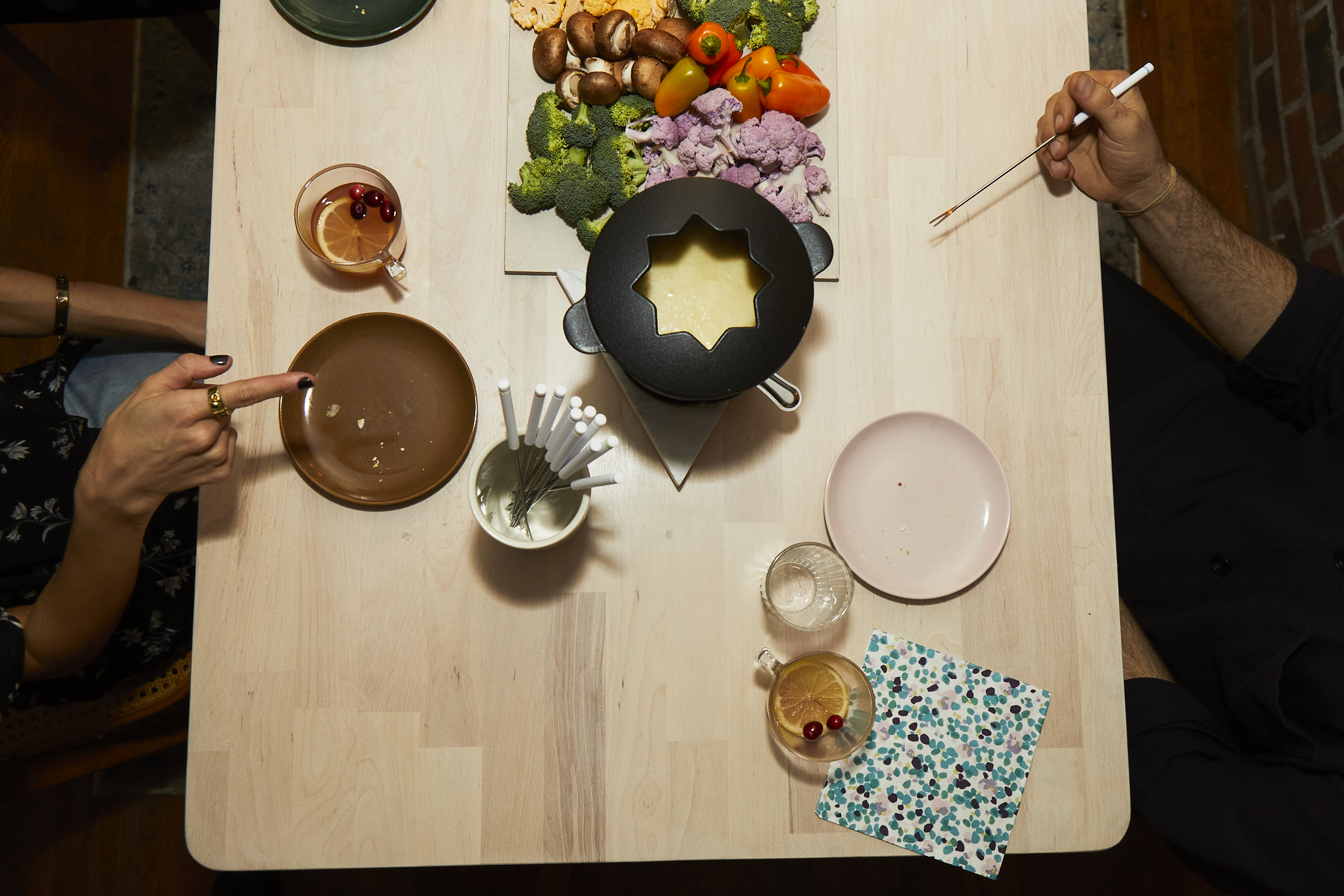 Overhead view of a wooden table with colorful plates.