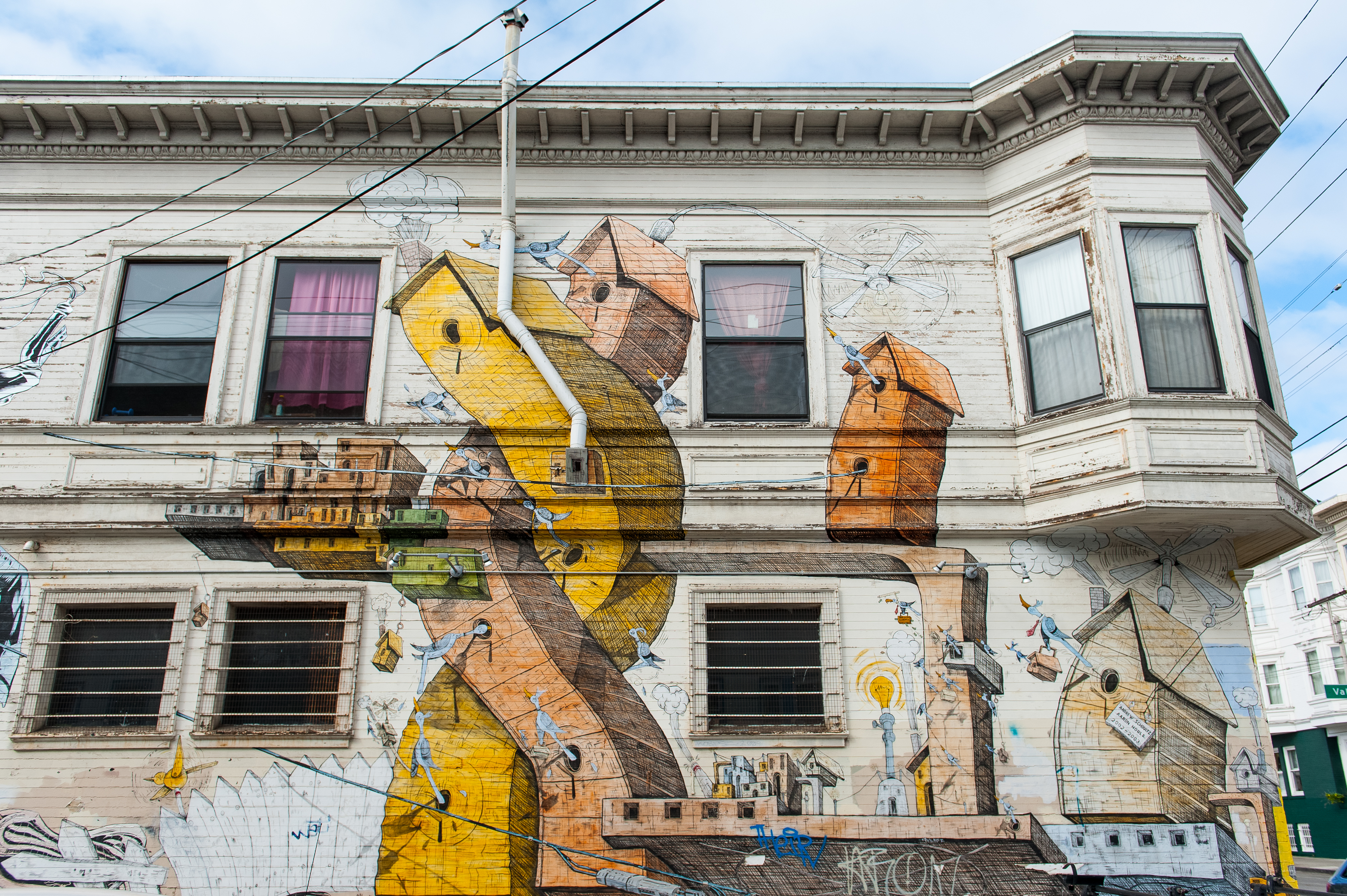 A mural on the side of a Victorian building depicting birdhouses in twisted shapes.