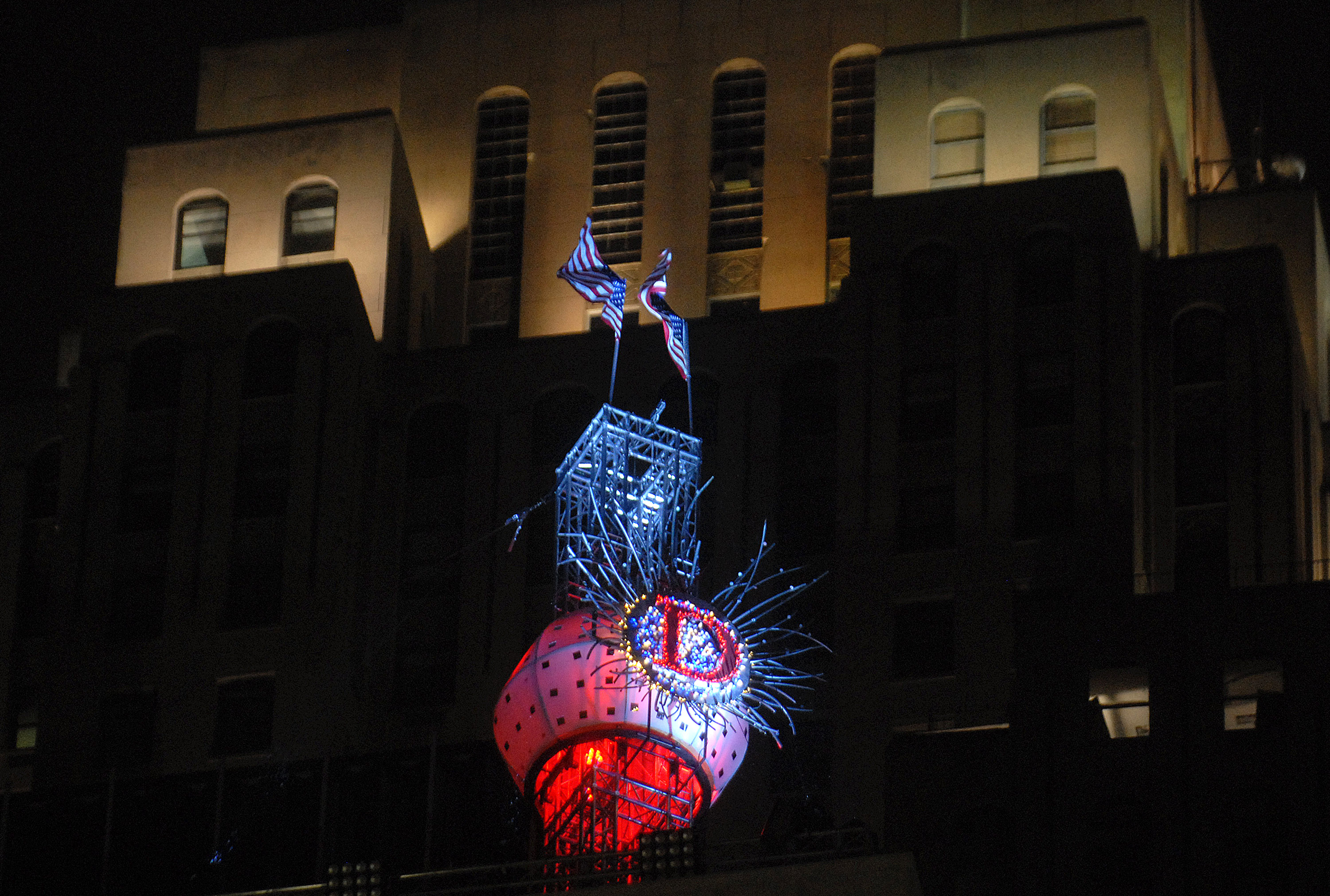 """A round, brightly lit ball with a """"D"""" on the outside in front of a tall building."""