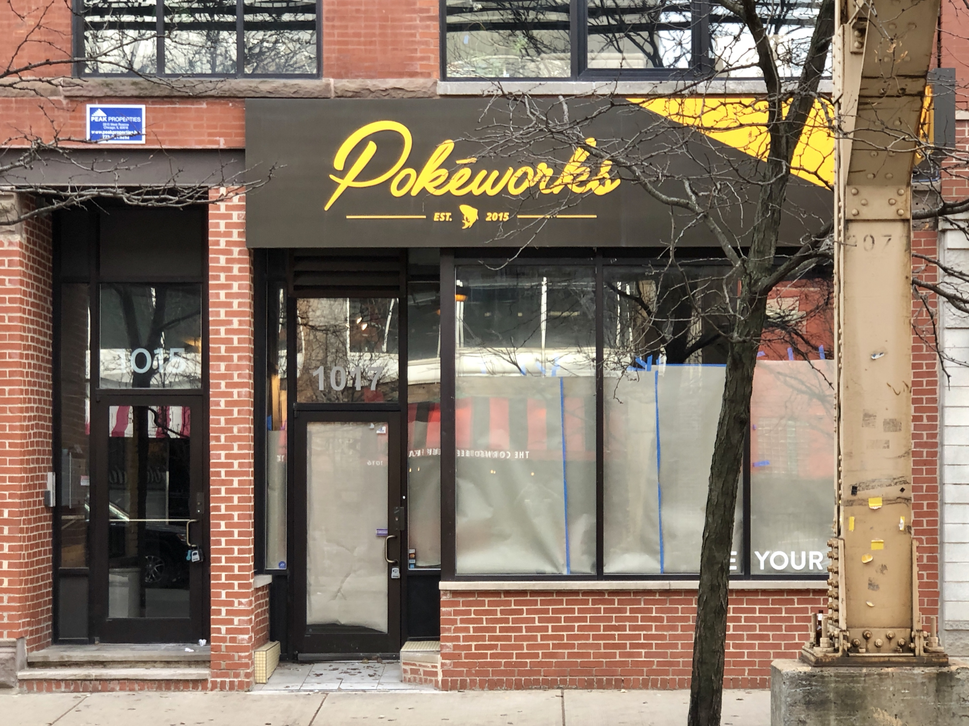 A papered-up storefront with a brown and yellow sign and windows.