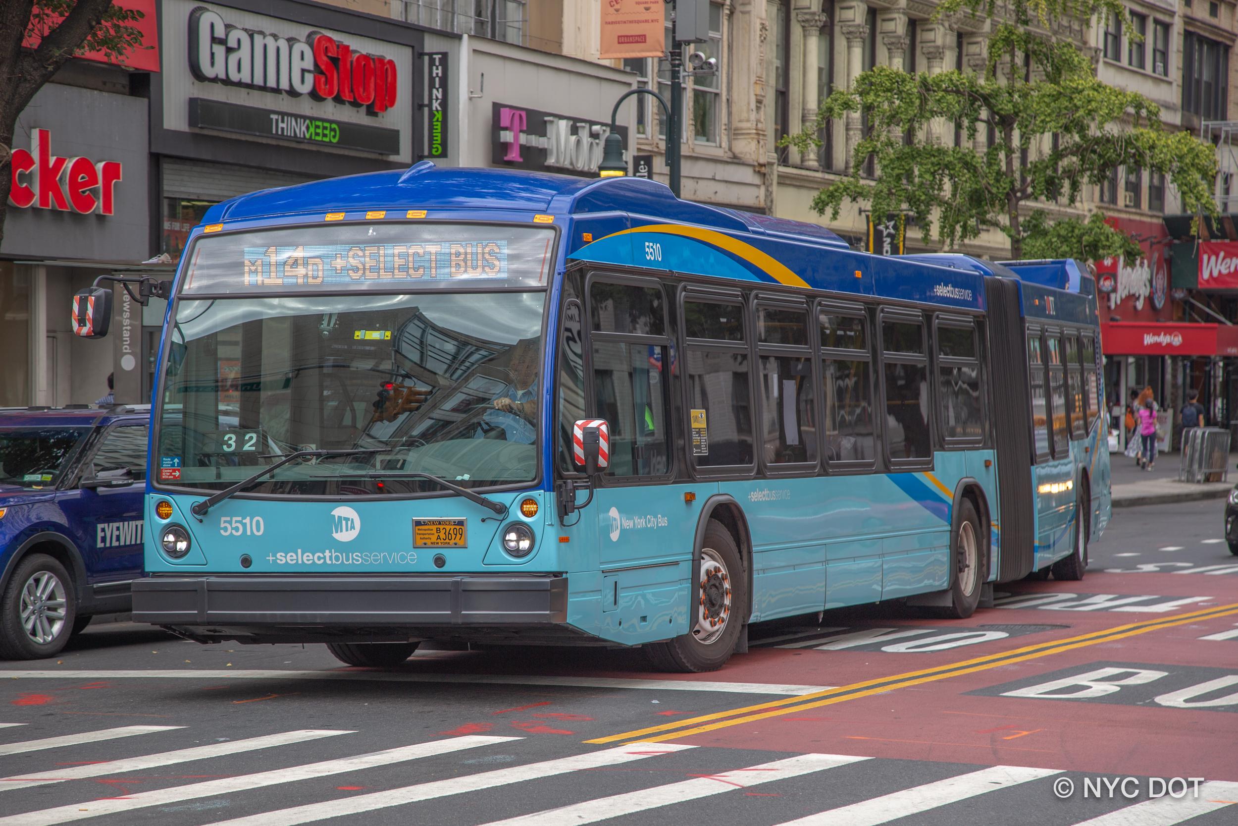 A blue New York City bus running through a busy Manhattan street.