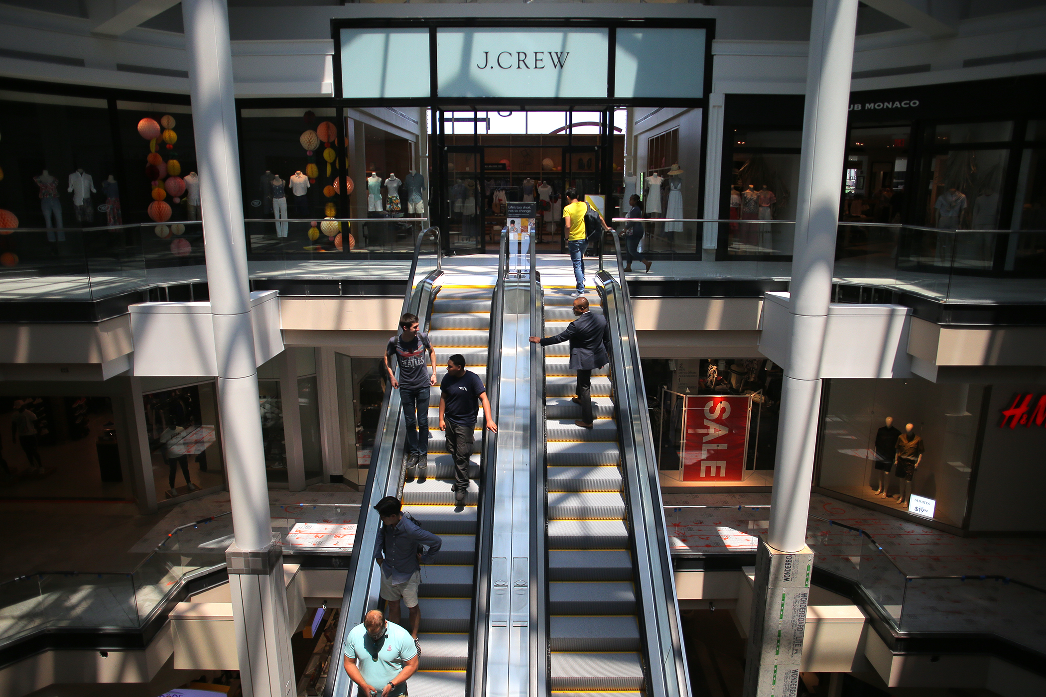 A wide shot of a pair of mall escalators in an airy mall with shops visible; and there are people on the escalators.