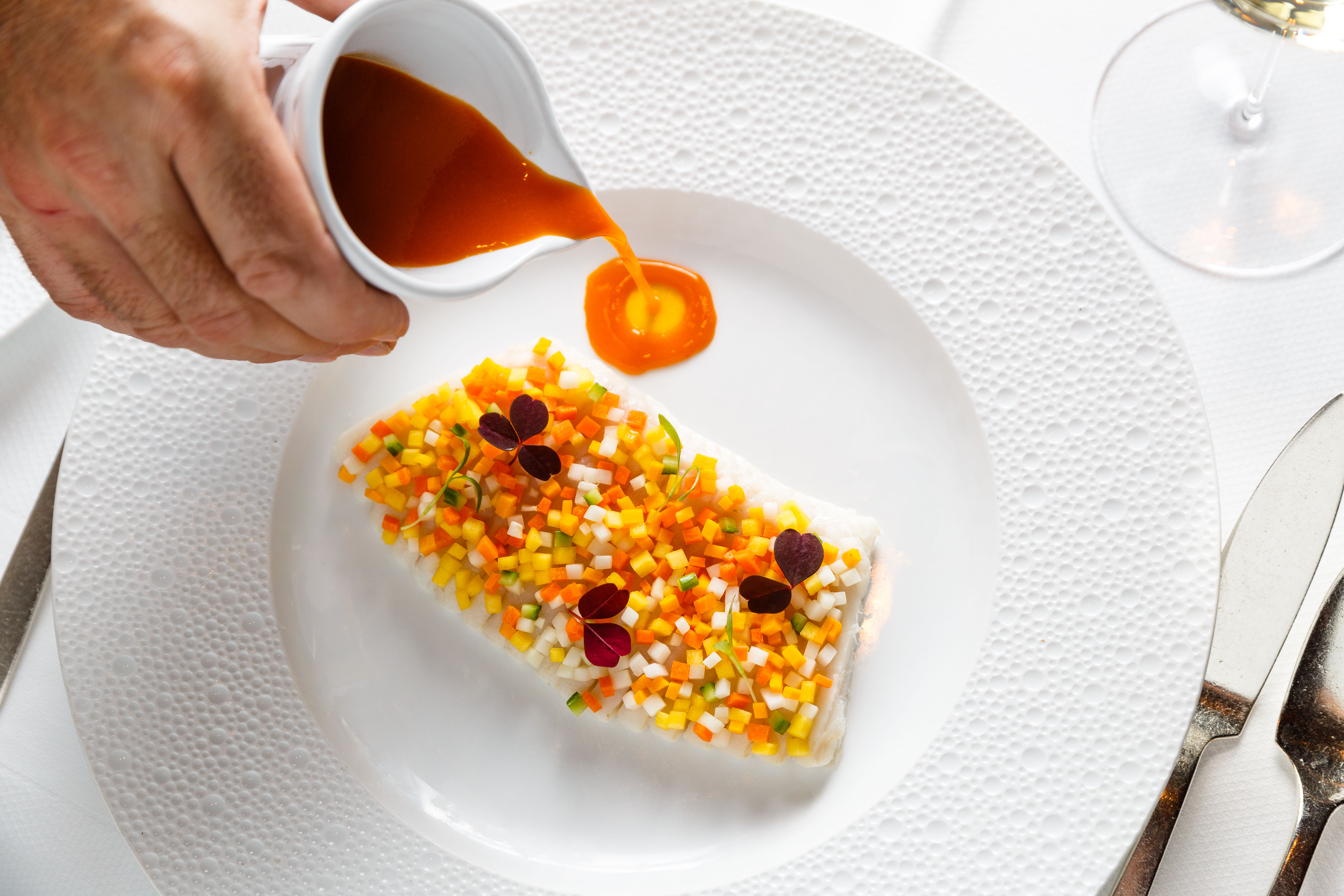 A server pours orange Thai shellfish broth onto a white plate, which holds a slide of poached skate covered by a multi-colored dice of papaya and squash