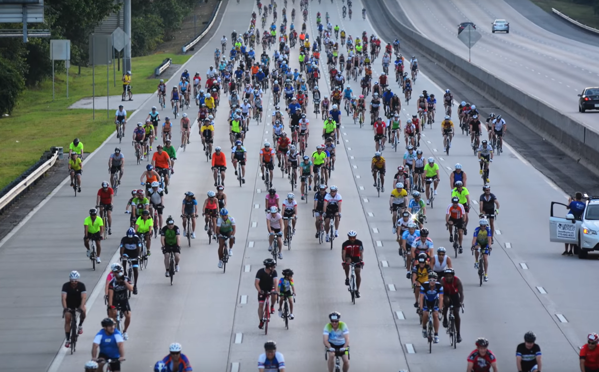 A swarm of cyclists pedal down the interstate.