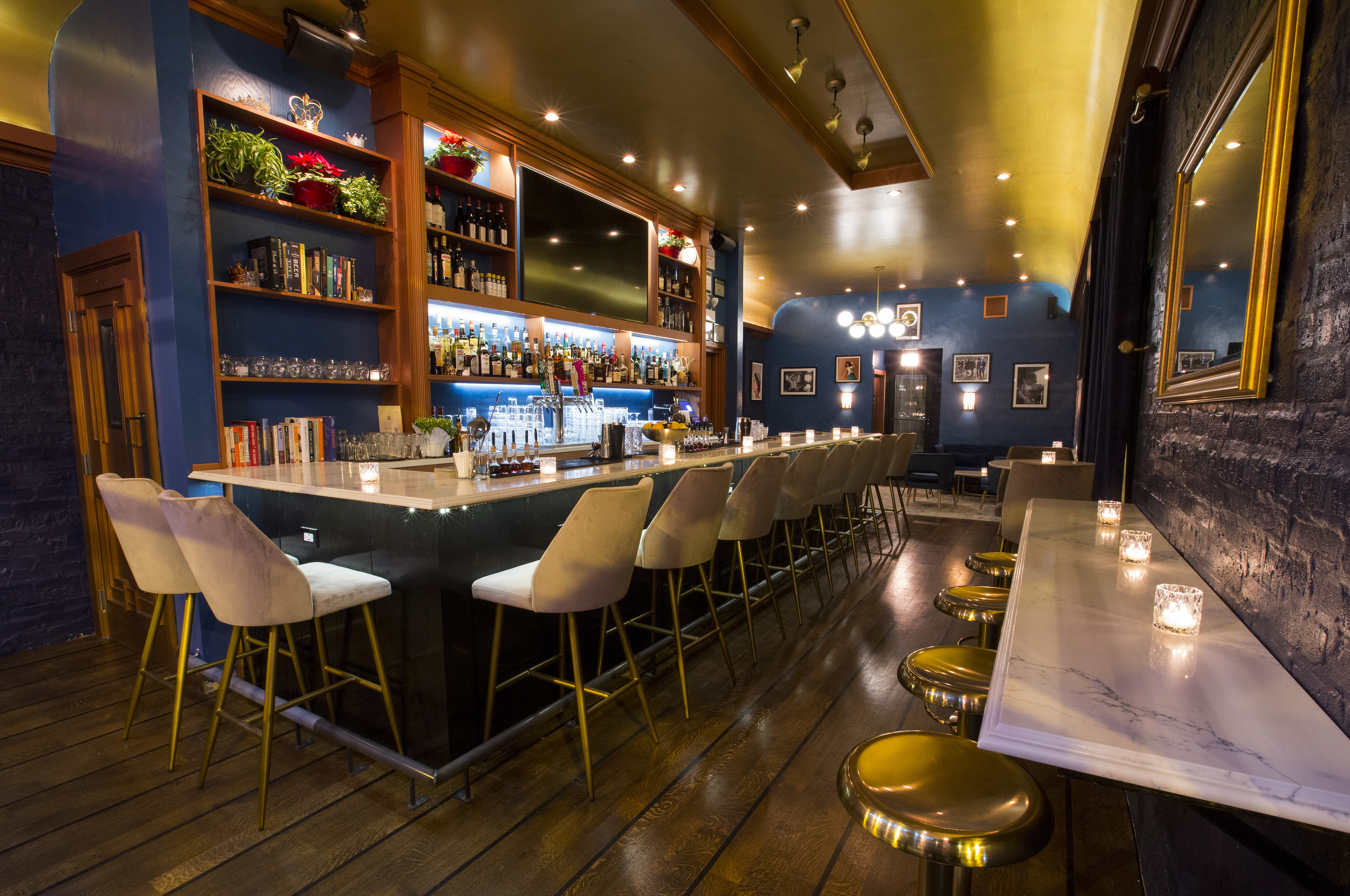 A bright bar space with blue walls and a white bar with brass stools and white backed seats.