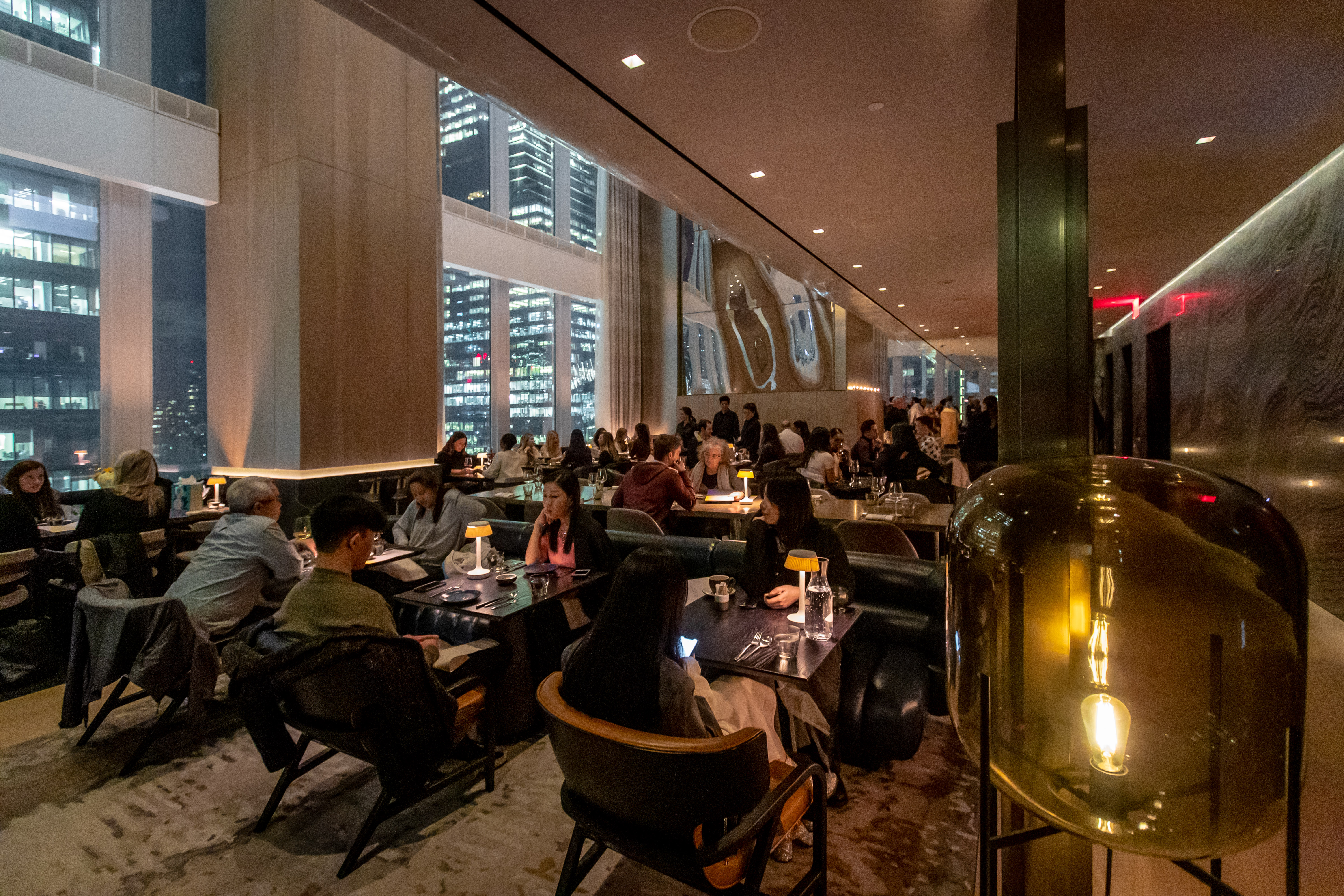 Patrons dine at tables at the Electric Lemon dining room, whose windows overlook Hudson Yards