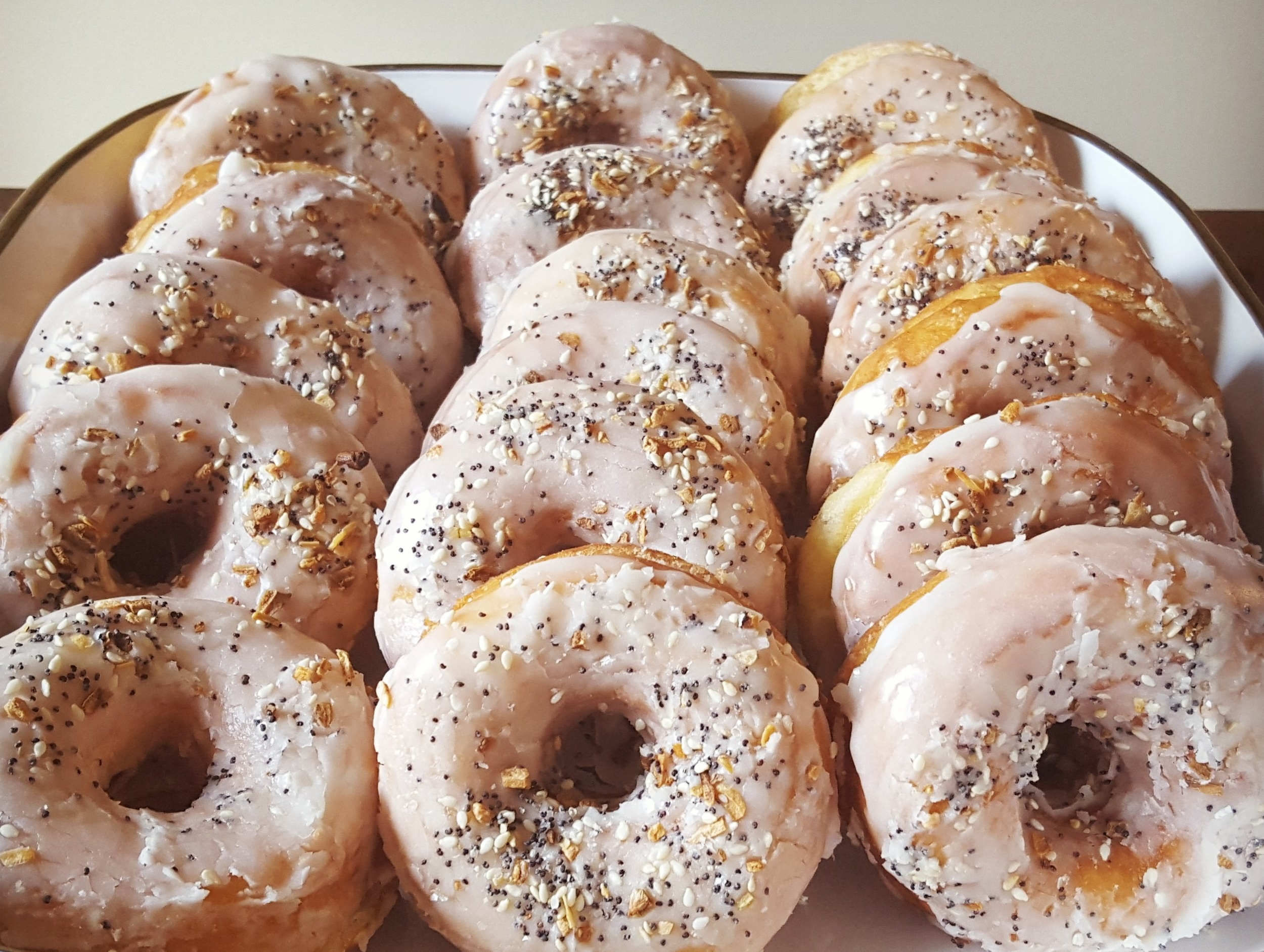 Rows of vanilla glazed doughnuts topped with poppyseeds and more