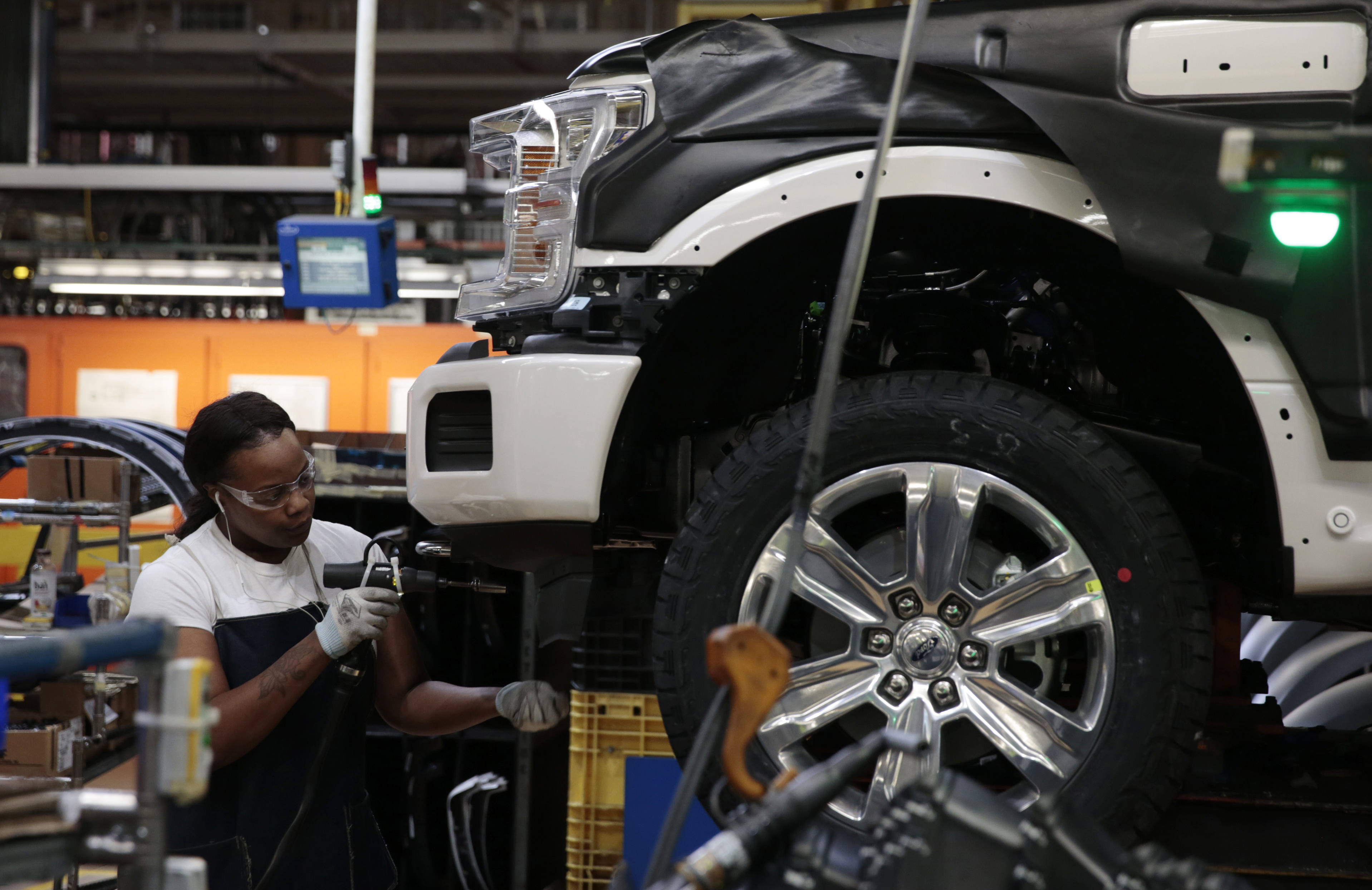 A factory worker adds something to the front fender on a partially finished white truck.