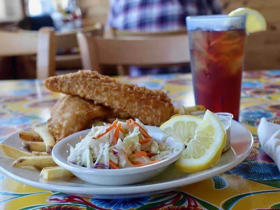 A picture of two breaded chunks of fish with medium-cut fries, a tiny bowl of slaw, and two lemon slices at Crazy Norwegian's