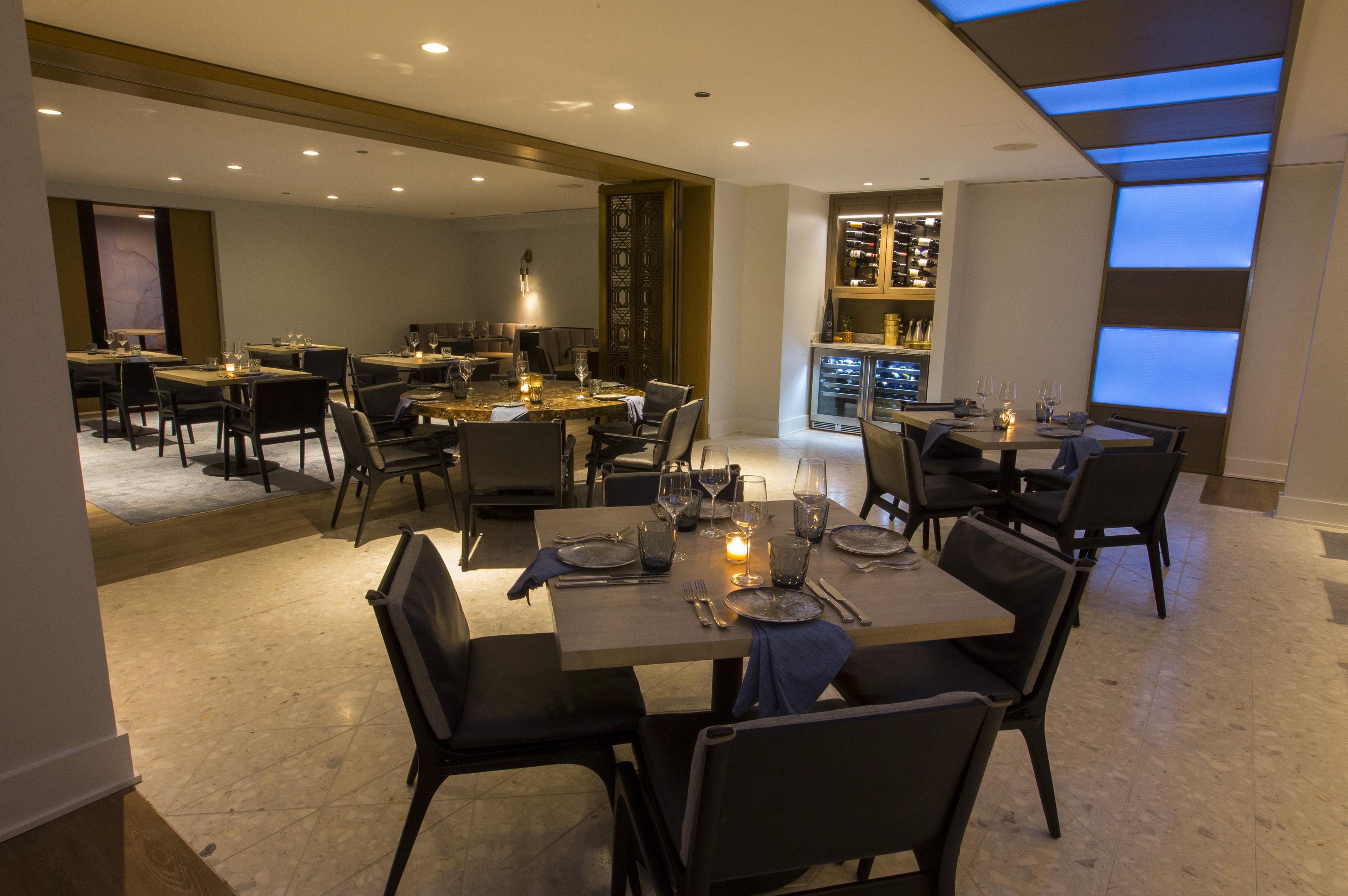 A dining room with a custom light fixture overhead.