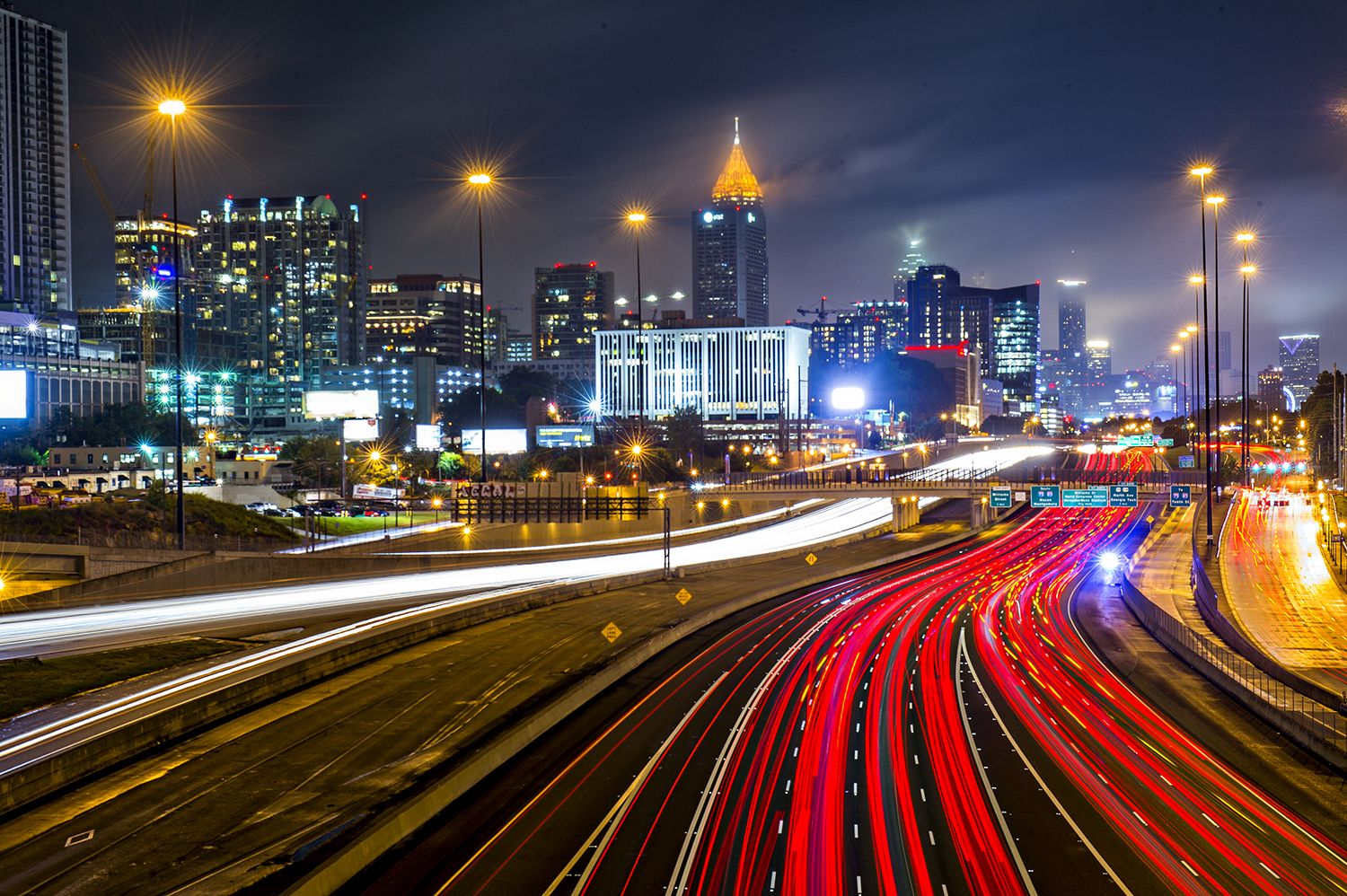 The skyline of midtown Atlanta is shown in the distance with traffic moving fast in the foreground.