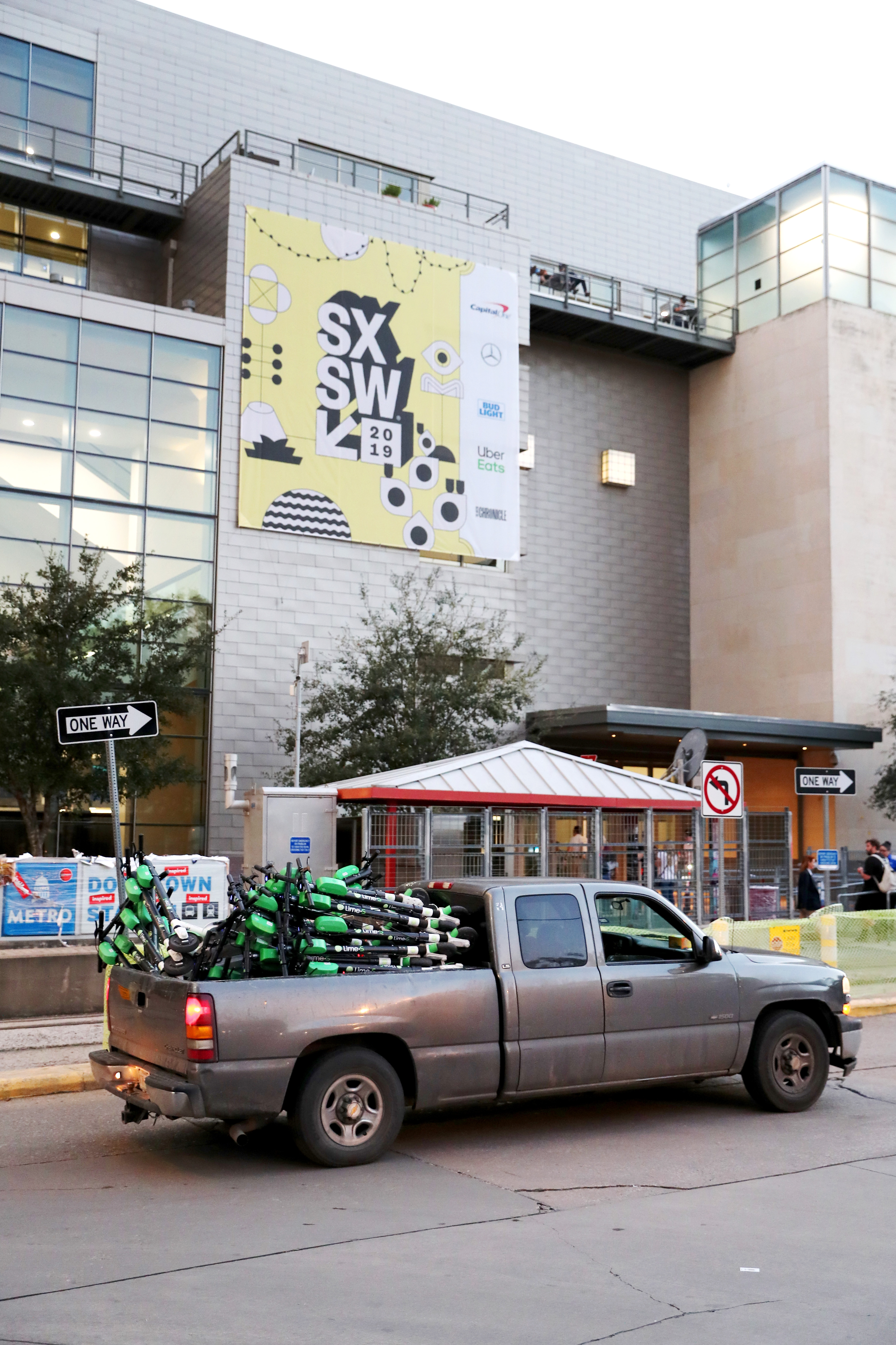 A truck full of e-scooters is parked on an asphalt street  in front of a small, covered commuter rail station. A five-story building with sign that reads SXSW is in the background. One-way street signs are on the sidewalk.