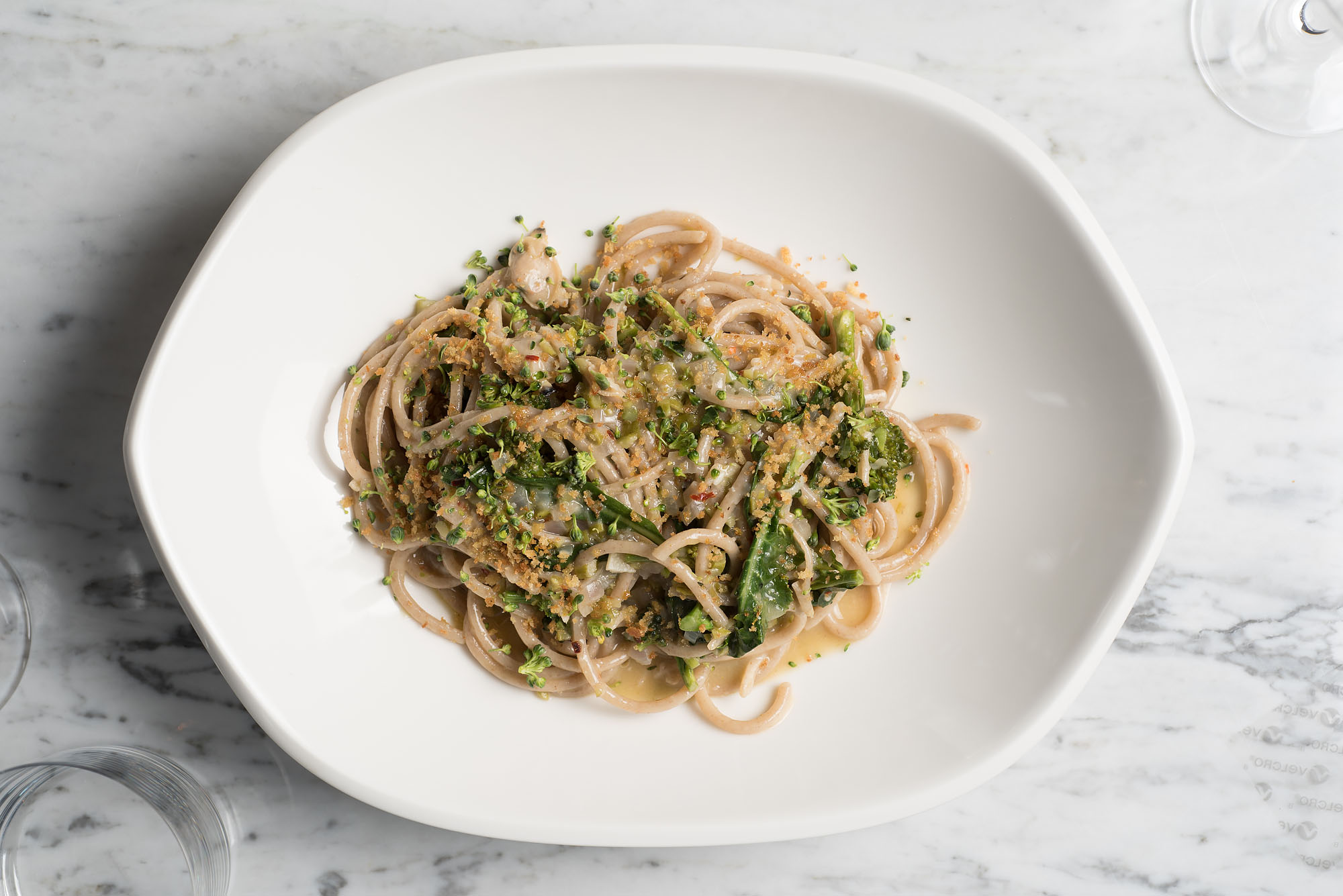 A plate of pasta with greens on a marble table at Cal Mare.