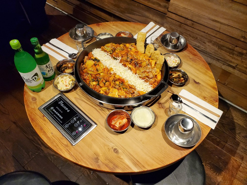 A cast iron pan filled with chicken and cheese on a round table