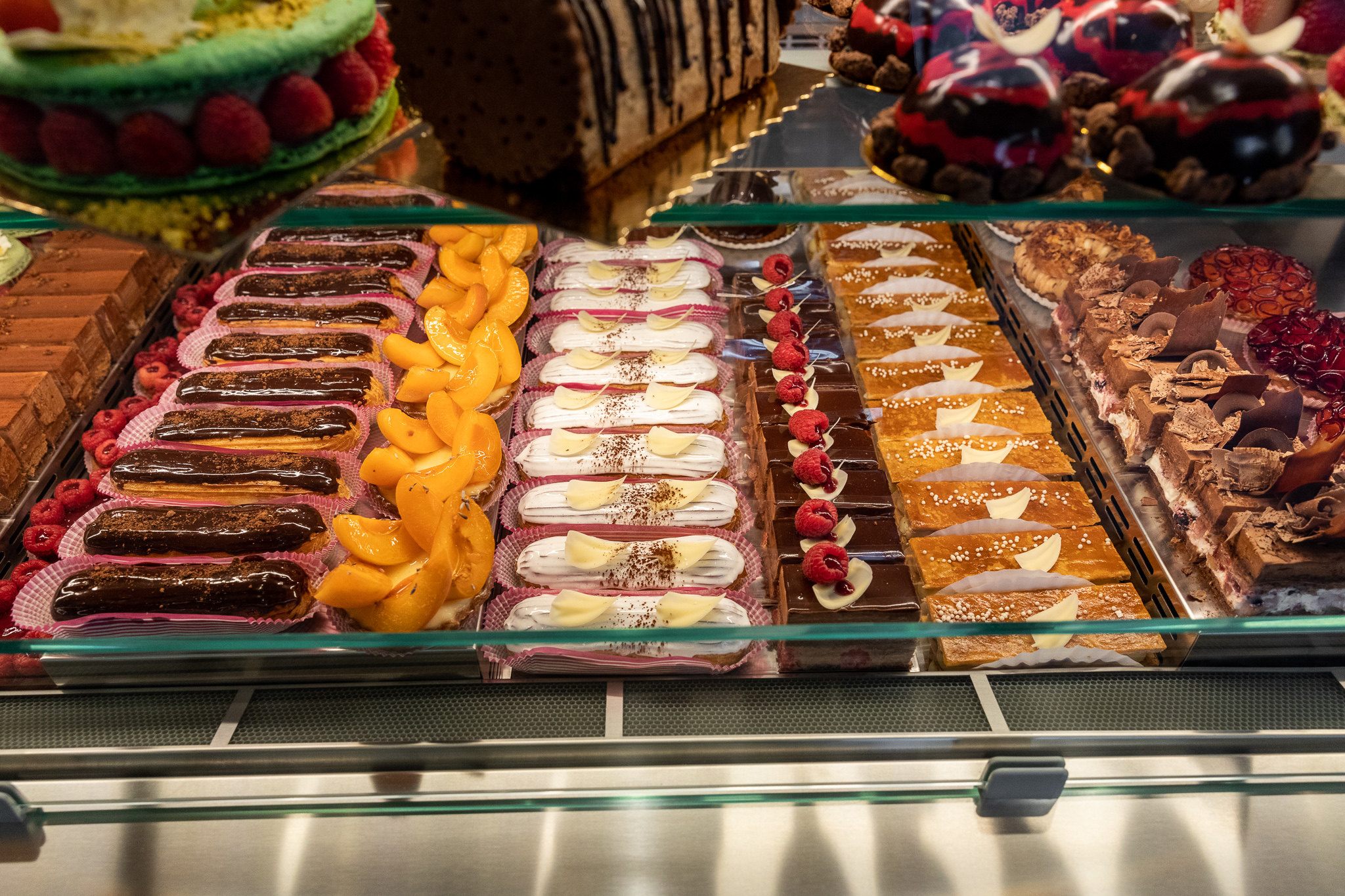 Rows of eclairs and other French pastries inside the Cannelle pastry case.