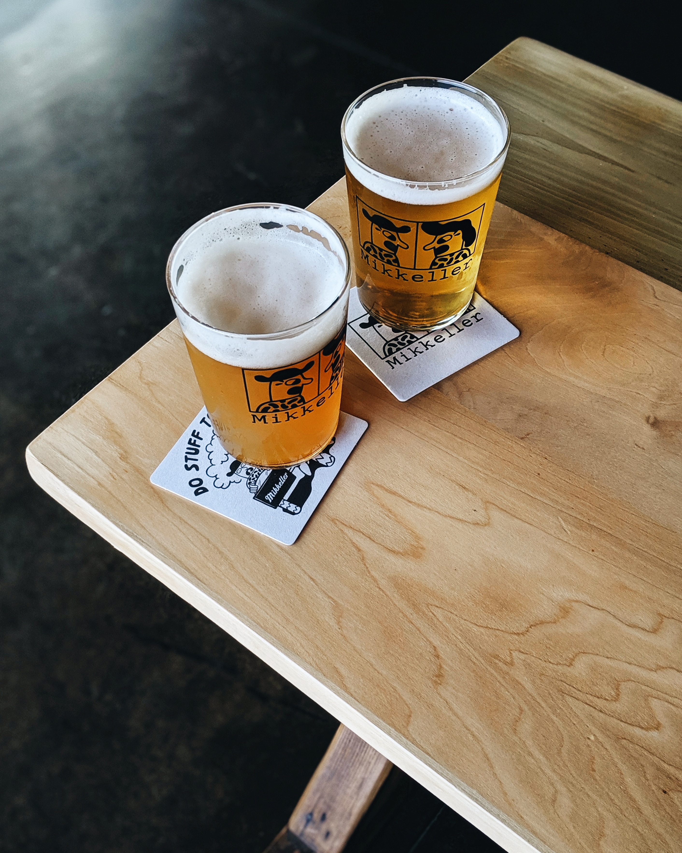 A picture of two pint glasses of Mikkeller beer on coasters, sitting on a wooden table at the Mikkeller pop-up space in Portland