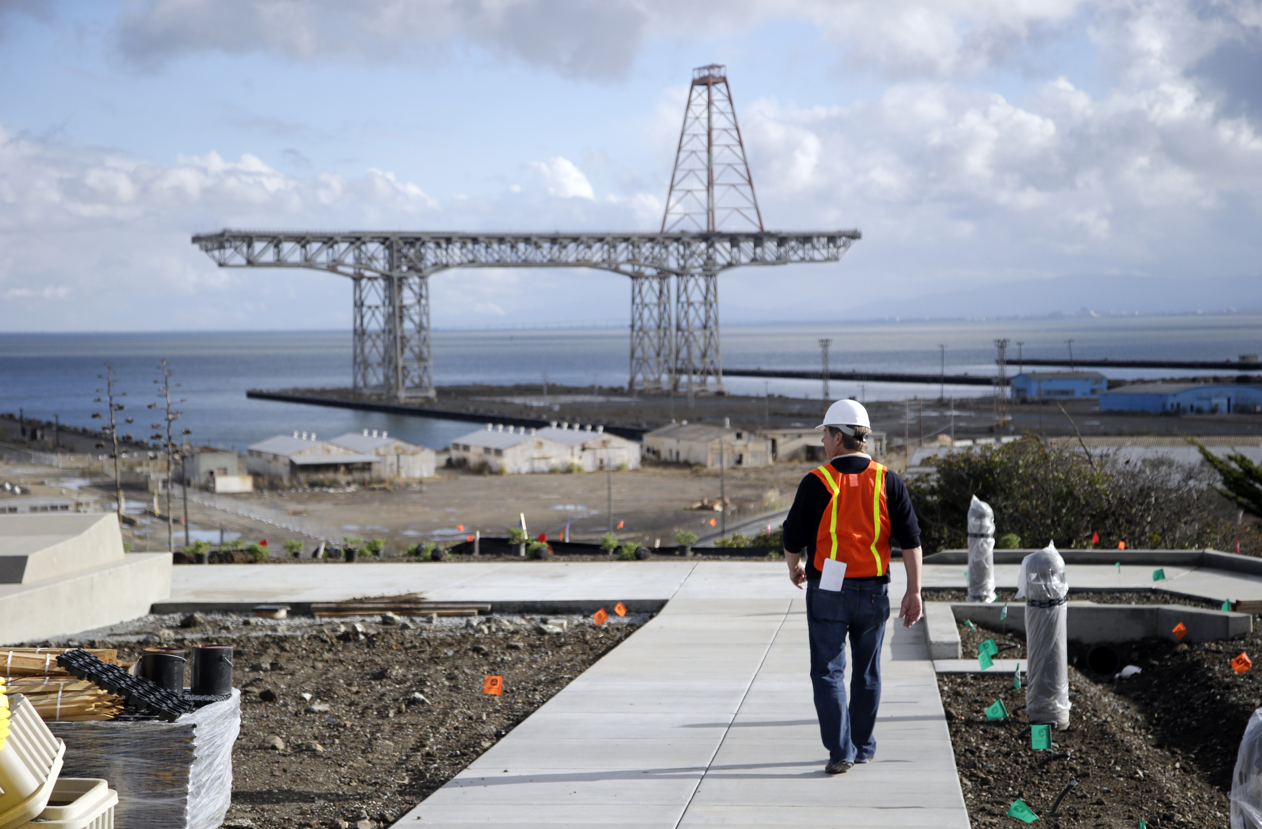 With the area's historic shipyard in the background, David Satterfield, spokesman for lead developer Lennar Urban, walks the grounds of the new San Francisco Shipyard homes development in the Bayview Hunters Point district