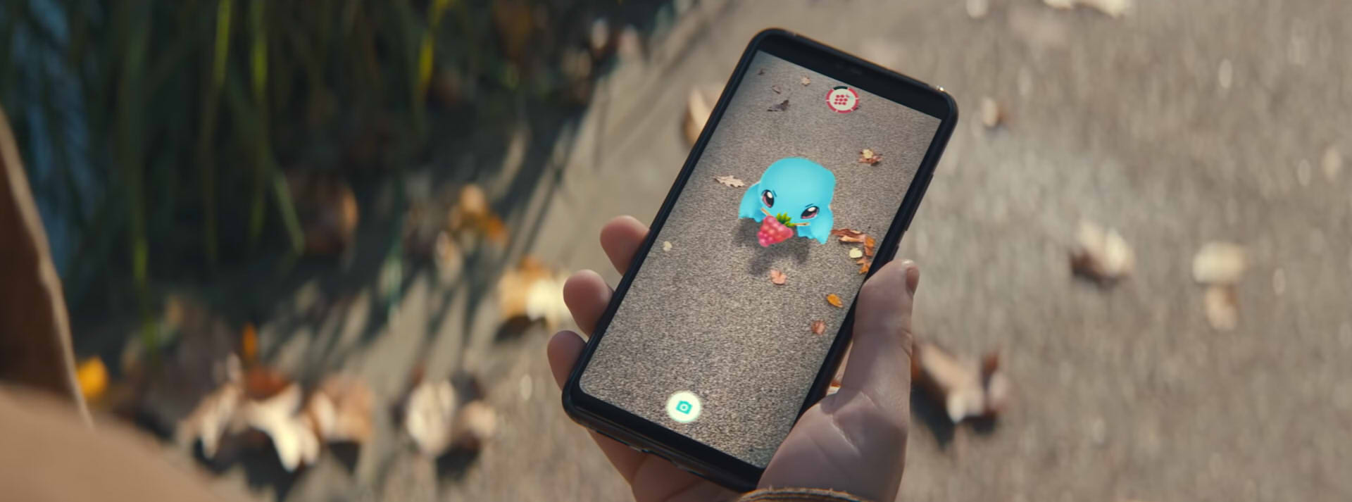 A hand holds up a phone, that has a Squirtle eating a berry on it