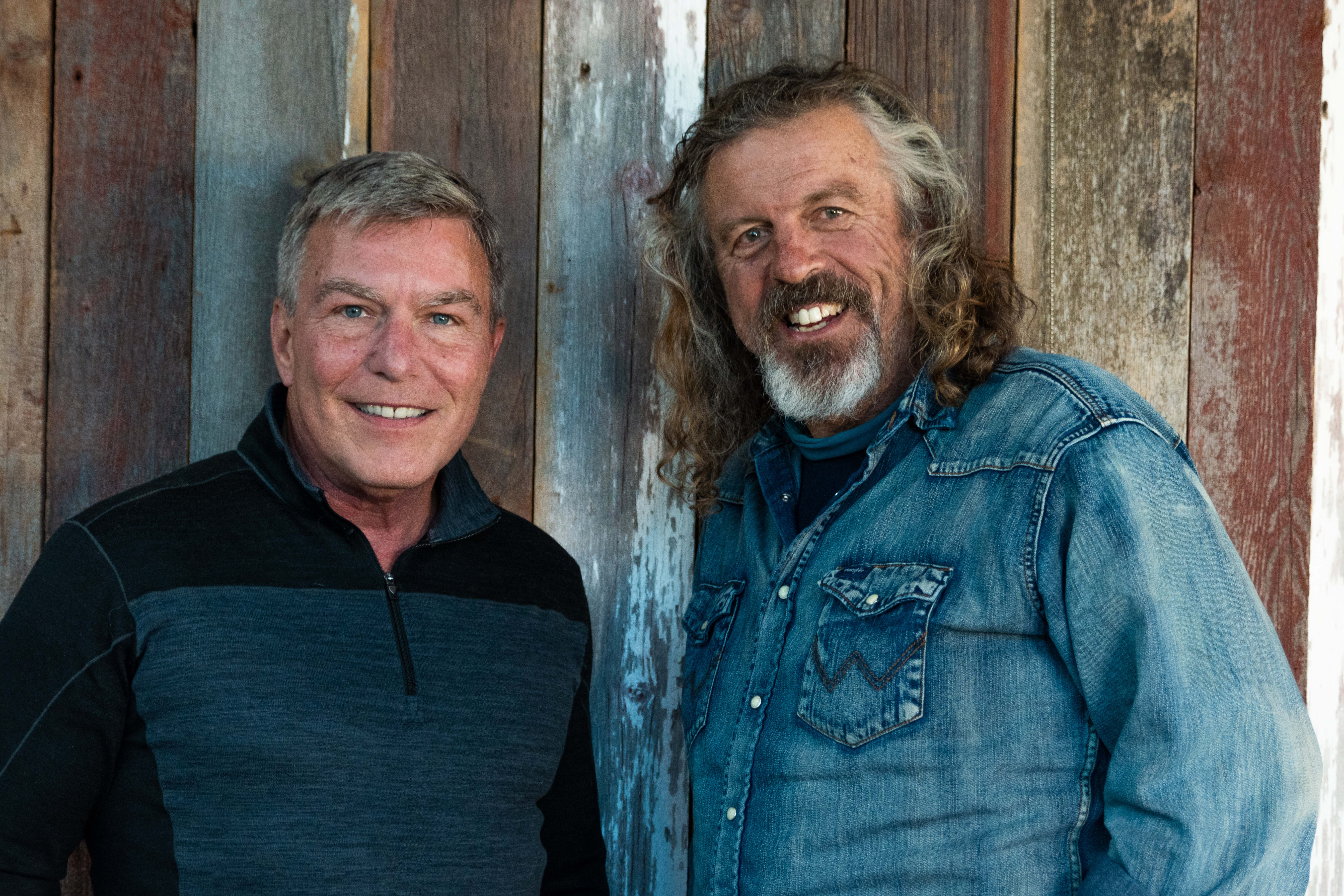 Tom Kamm wearing a dark blue button-down shirt standing next to Jack Gilmore wearing a denim button-down shirt in front of a wooden wall