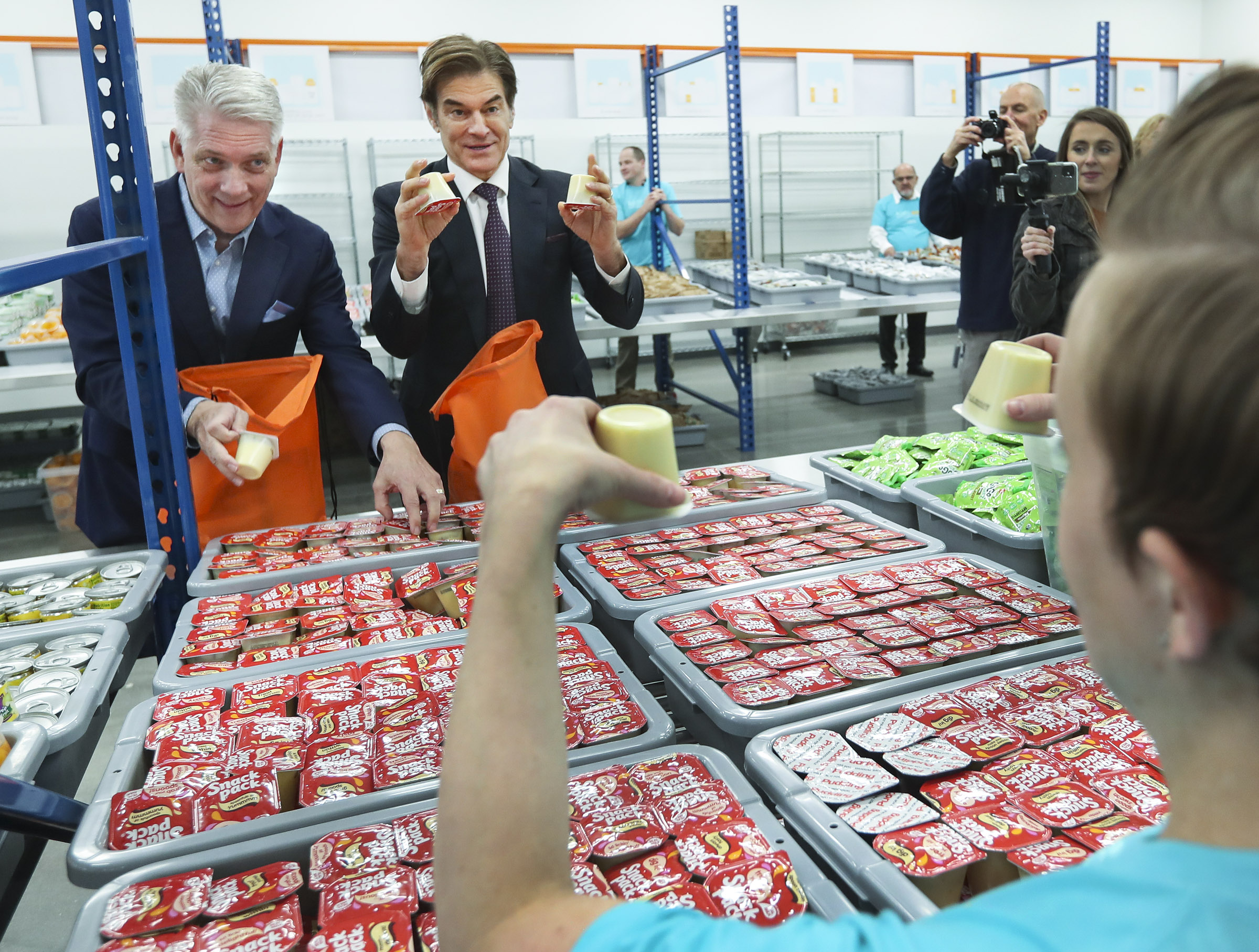 USANA CEO Kevin Guest, left, and Dr. Mehmet Oz fill bags with food as the USANA Kids Eat food-packing facility opens in West Valley City on Thursday, Dec. 19, 2019. To try to eliminate the issue of 1 in 5 Utah kids going home to no food, the organization will pack 1,000 backpacks with food for seven meals in them each week for distribution to 56,000 children in Utah.