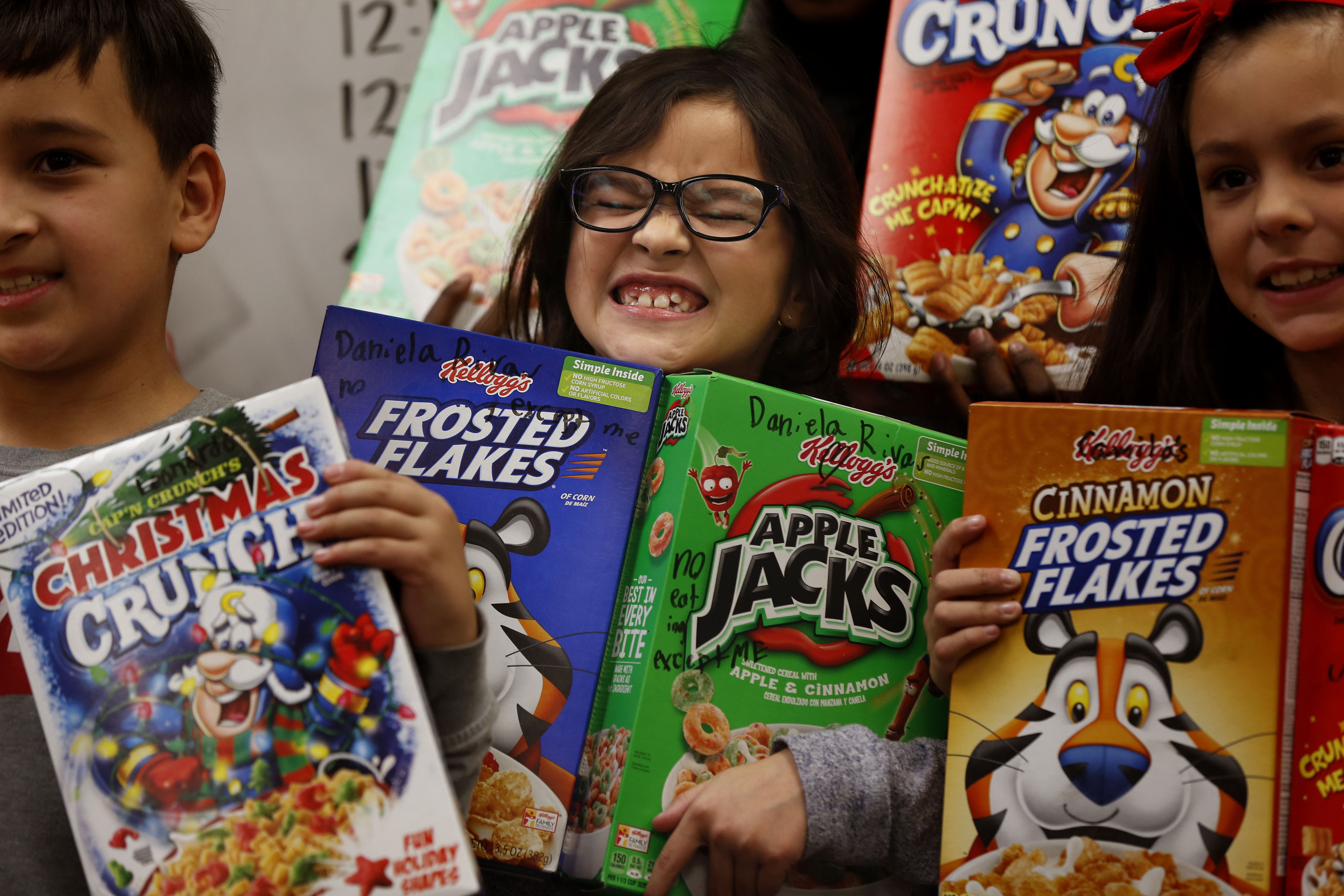 Third-grader Daniela Rivas, center, and her classmates display their two boxes of cereal that they were given at Oquirrh Elementary School in West Jordan on Thursday, Dec. 19, 2019.Principal Shauna Worthington surprised her students with the gift of breakfast over the holiday break, giving out 15,000 boxes of cereal at the school.