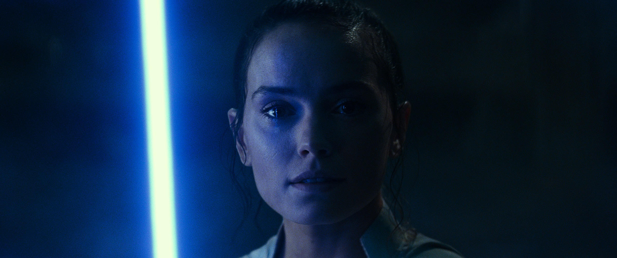 Rey lights up her lightsaber in a pitch-black temple.