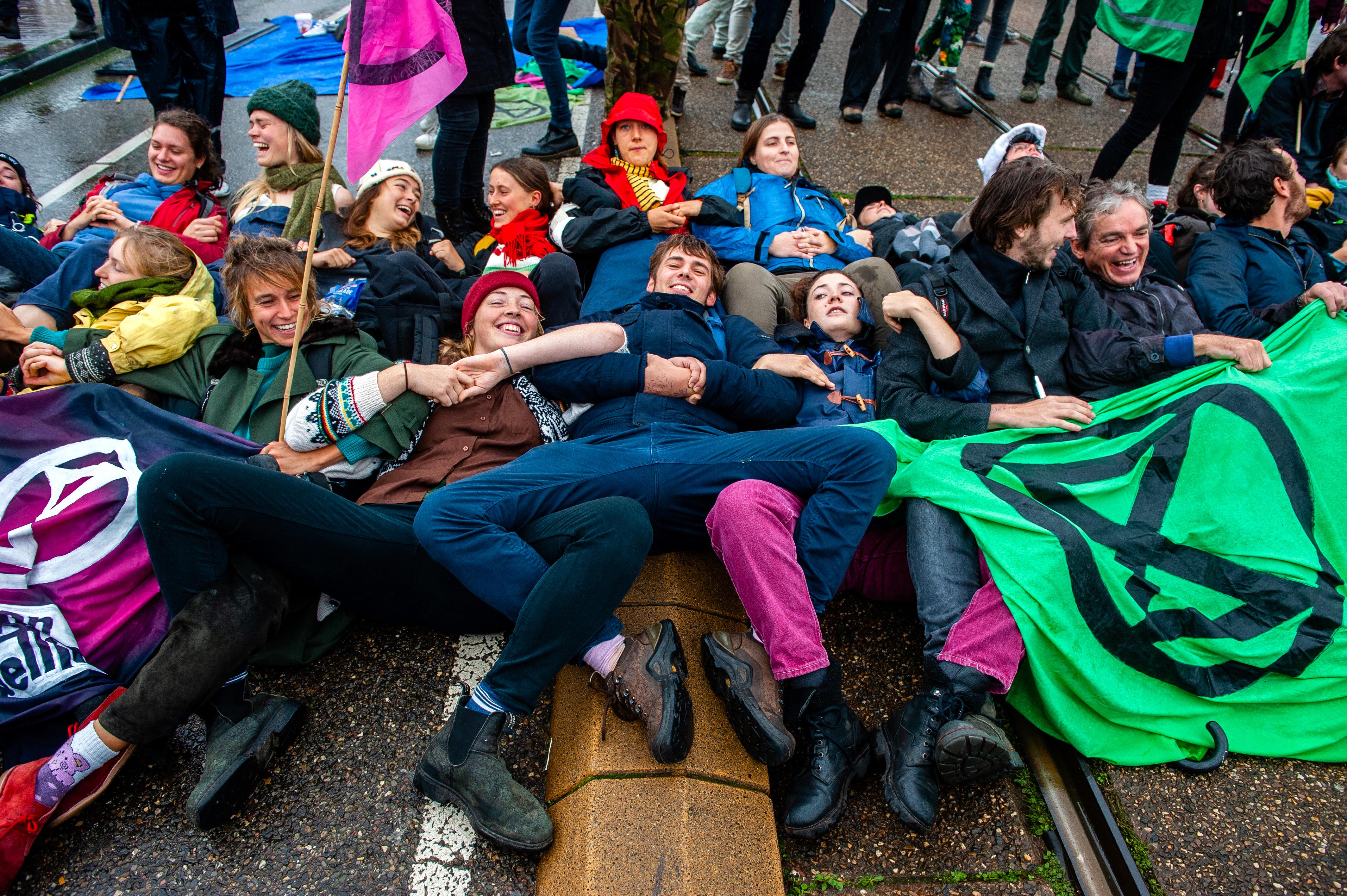 Smiling Extinction Rebellion activists block a bridge in Amsterdam.