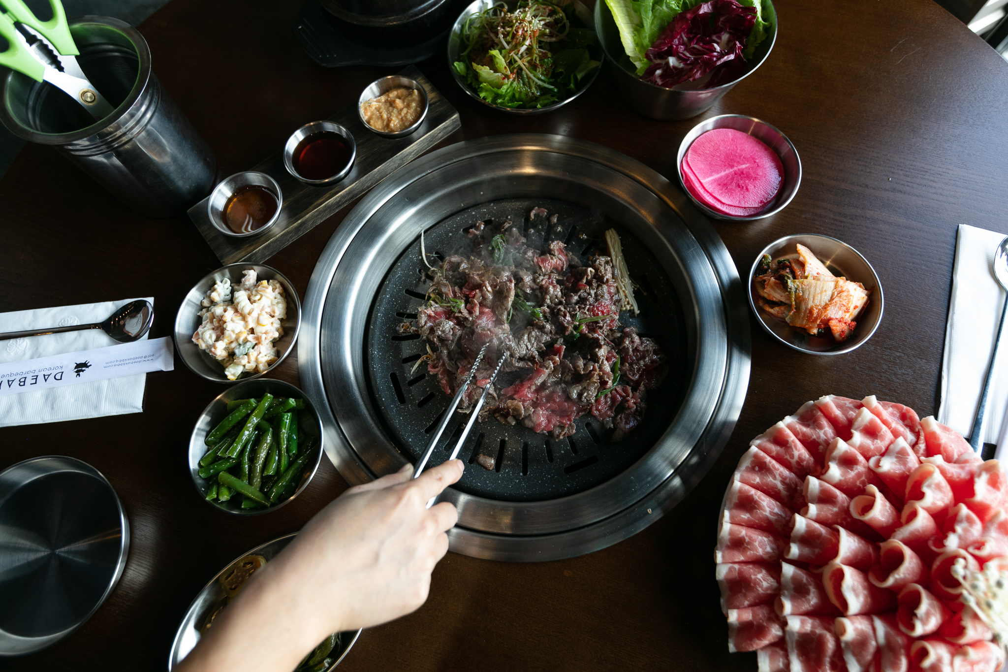 A hand reaches in with metal tongs to cook thinly sliced beef on a hot, circular grill at Daebok.