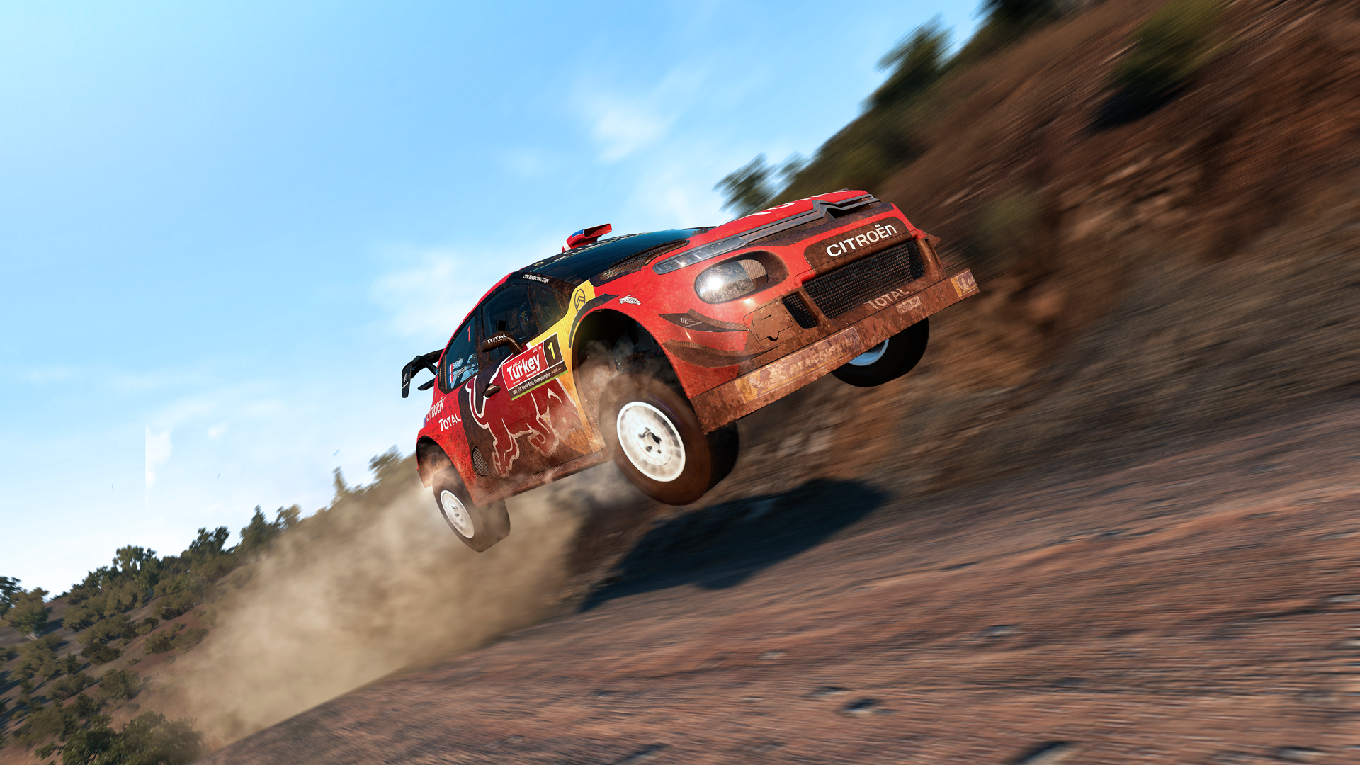 A red rally car, dust trailing behind it, soars over a jump and through the air.
