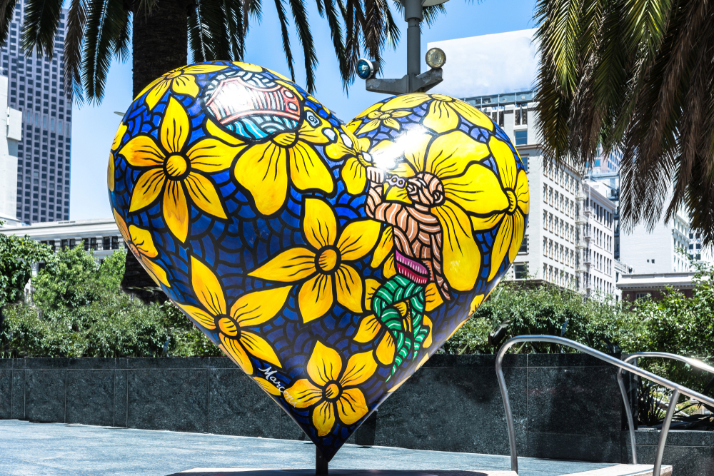 A giant heart sculpture painted with yellow flowers.