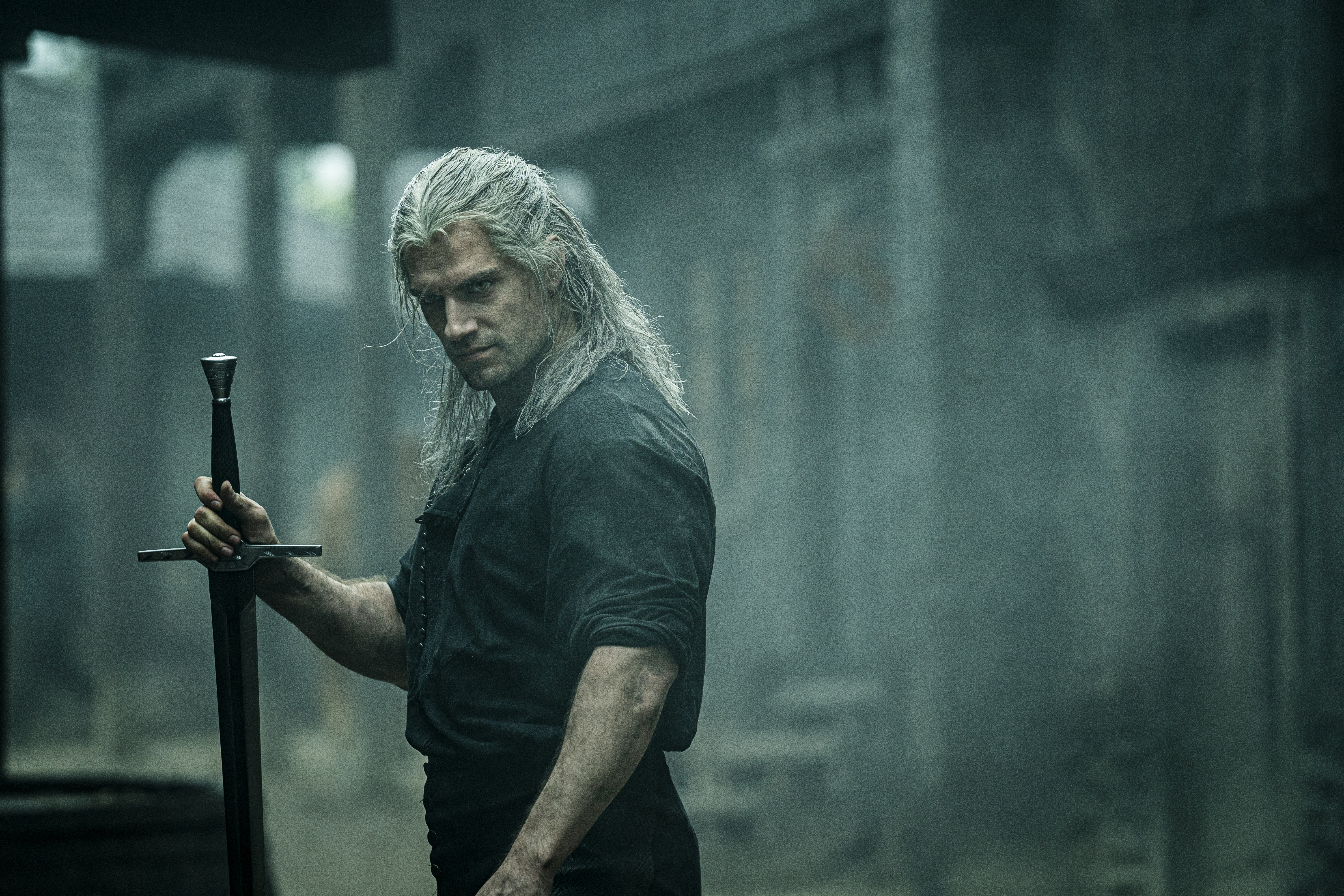 Geralt of Rivia, a brawny gray-haired man, holds a sword upside down by the hilt in The Witcher