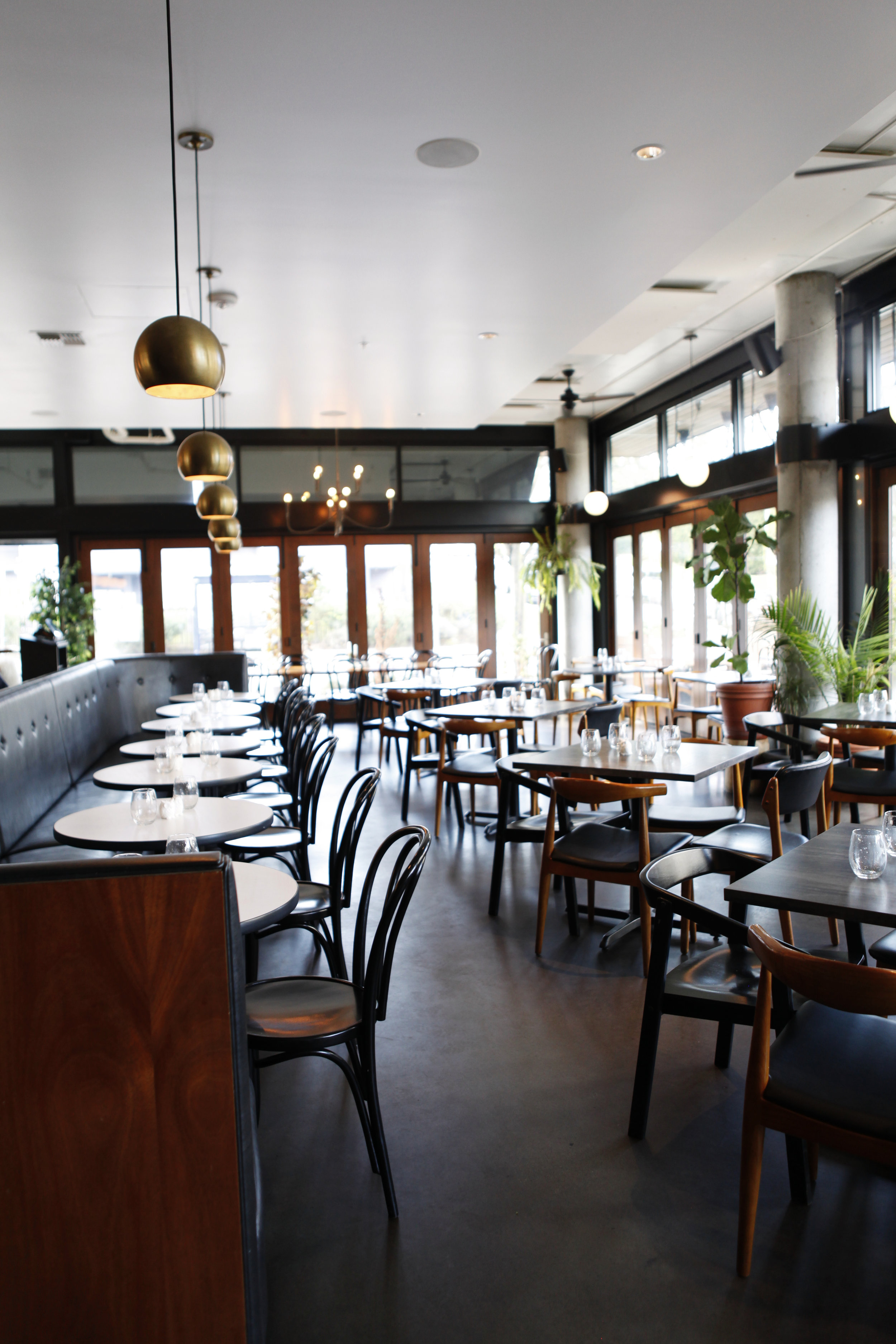 The empty, light-filled dining room at Tallulah's, with wooden chairs and tables.