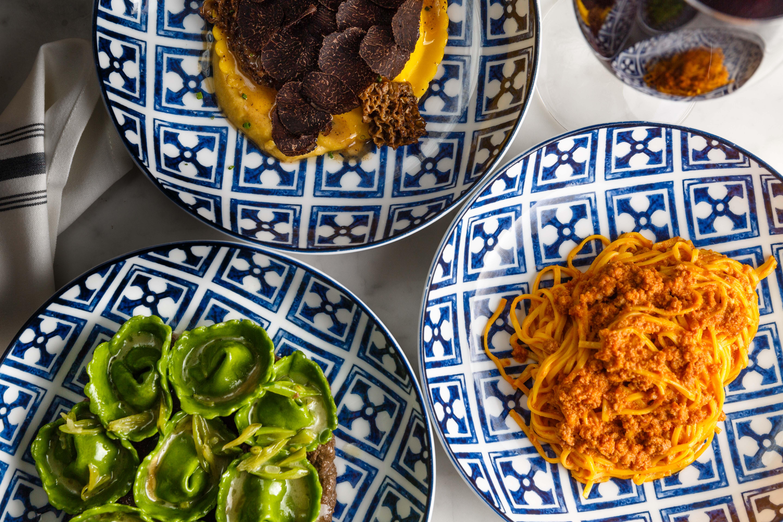 Uovo pasta, cappelletti, tagliolini al ragu sit on elegant blue and white plates at Rezdora.