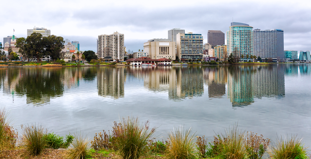 Mid-rise buildings reflected on the surface of a lake in the foreground.