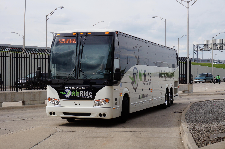 """An """"Air Ride"""" bus travels down a road near a freeway."""