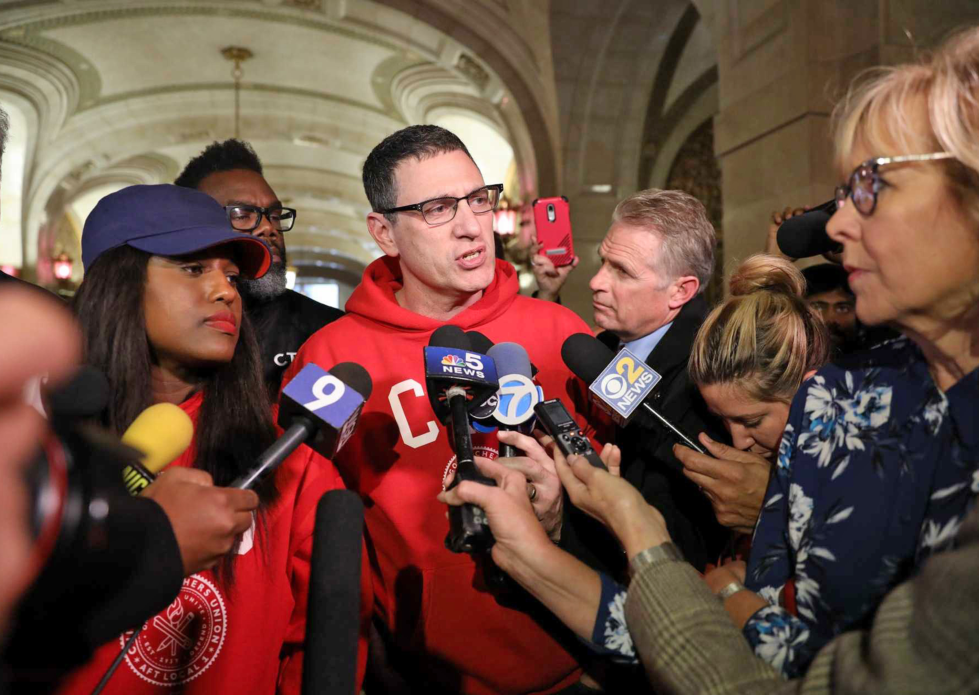 Chicago Teachers Union president Jesse Sharkey (red sweatshirt) and vice president Stacy Davis Gates (blue cap) at a news conference after the 2019 teachers strike ended.