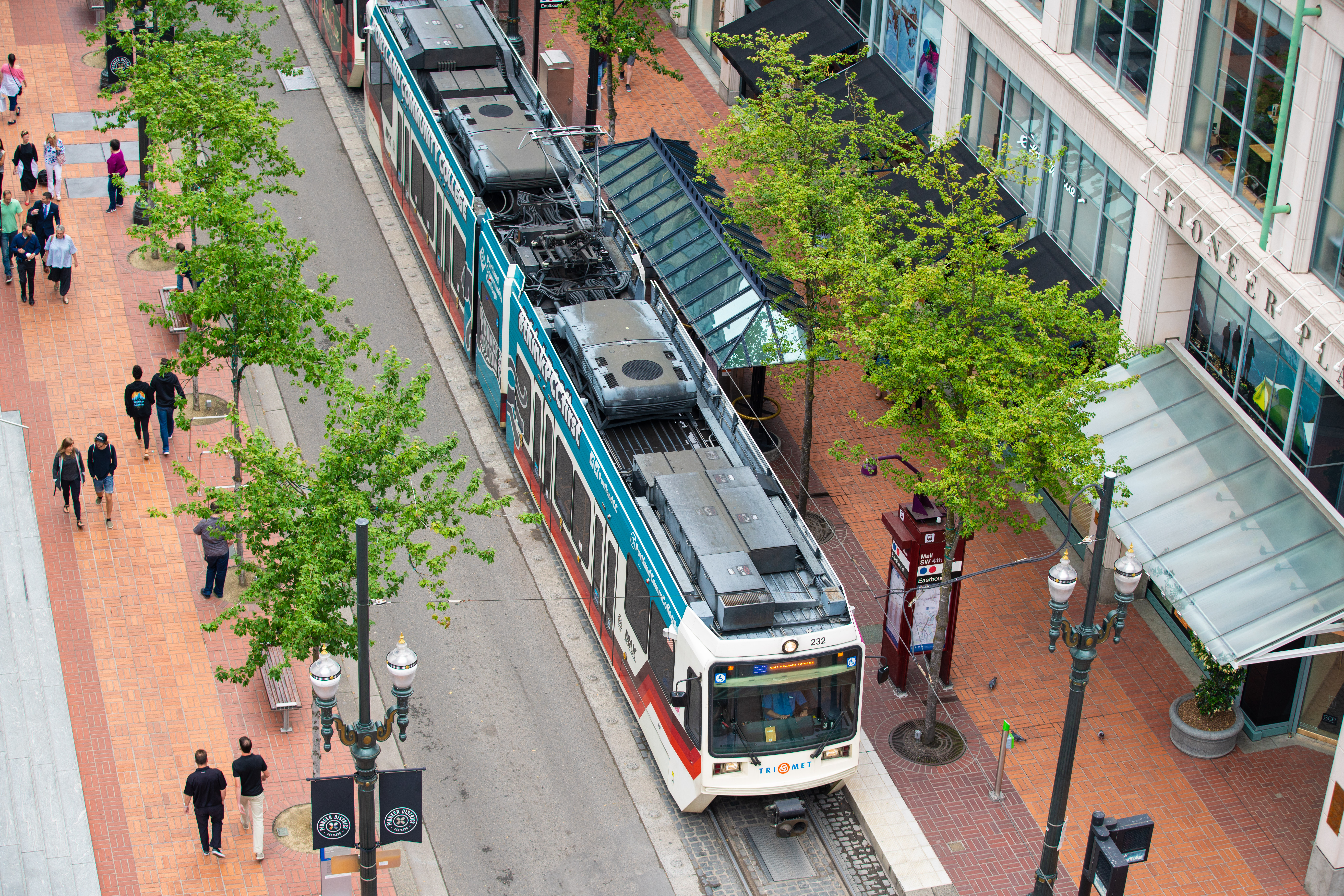 A white Trimet train arriving to the station in downtown Portland, with people walking on a wide sidewalk to the left.