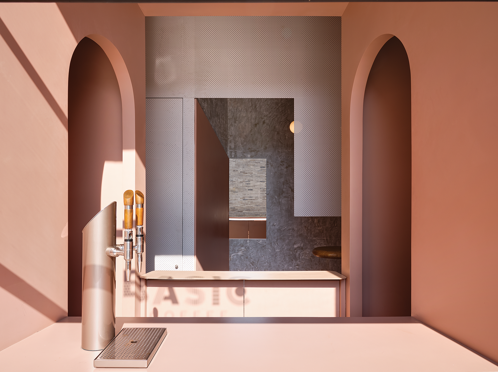 Blush pink coffee bar with arched walls and two counters.