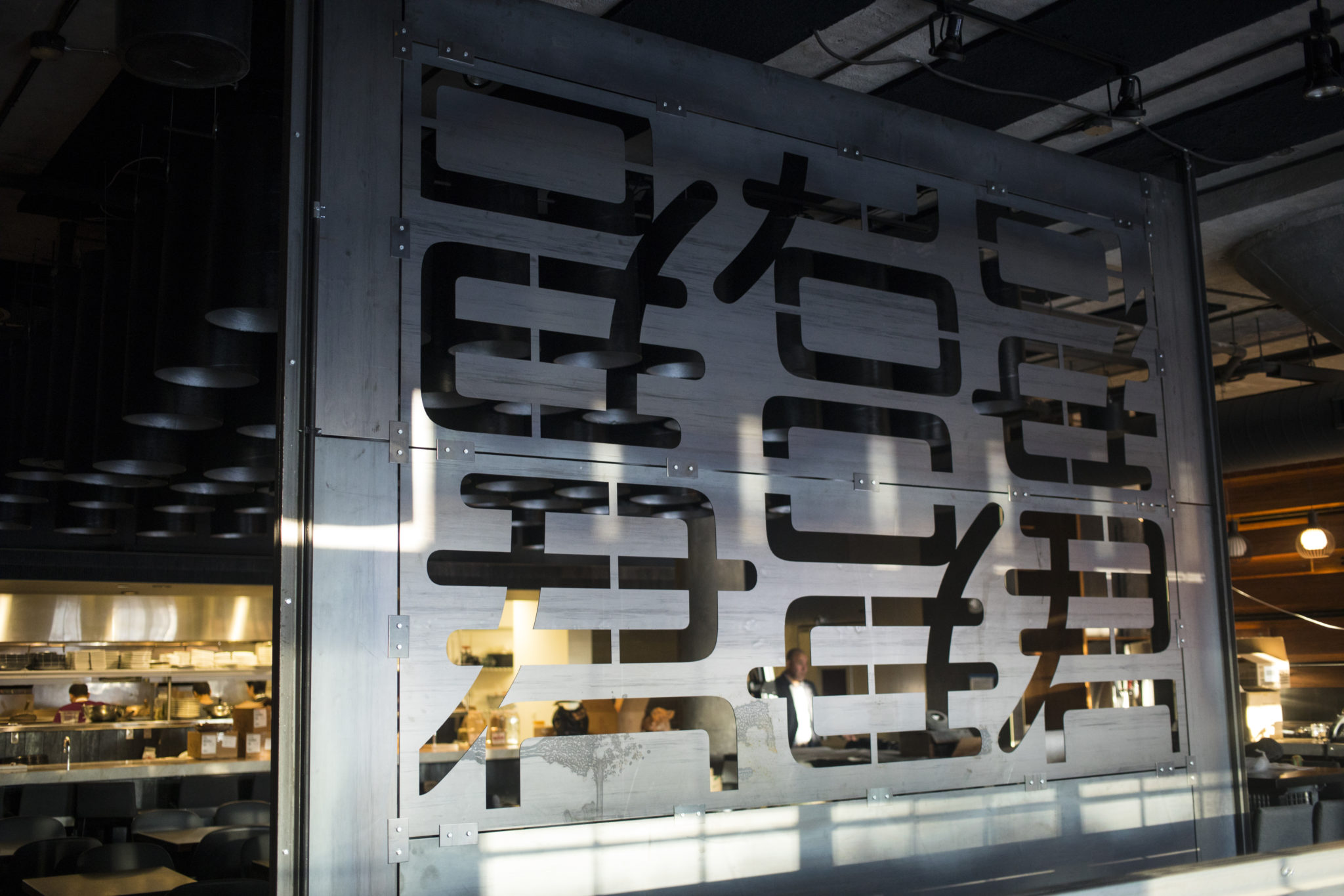 A glass wall with charachters etched onto it in the dining room at JUN