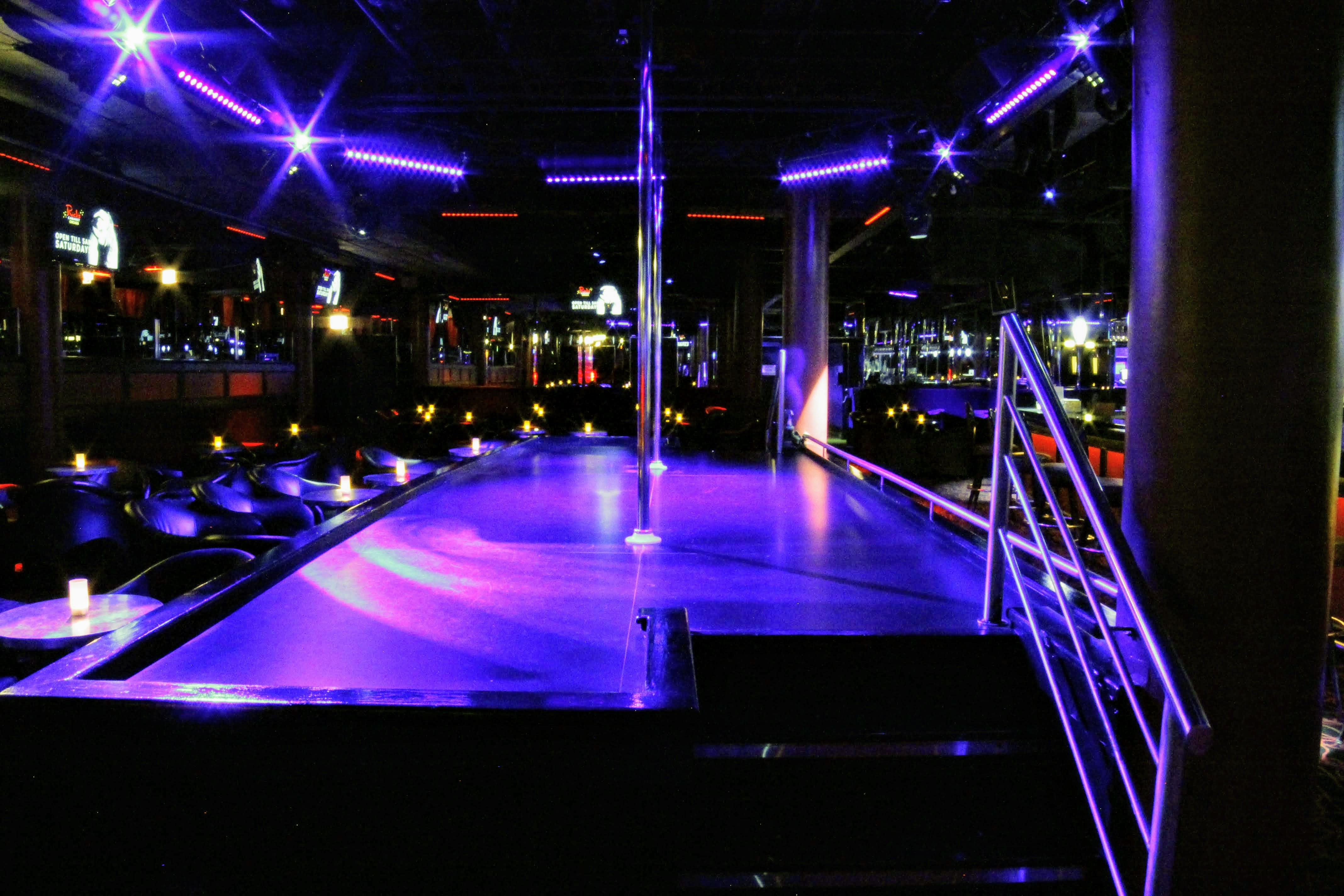 An empty strip club with a stage and pole surrounded by chairs.