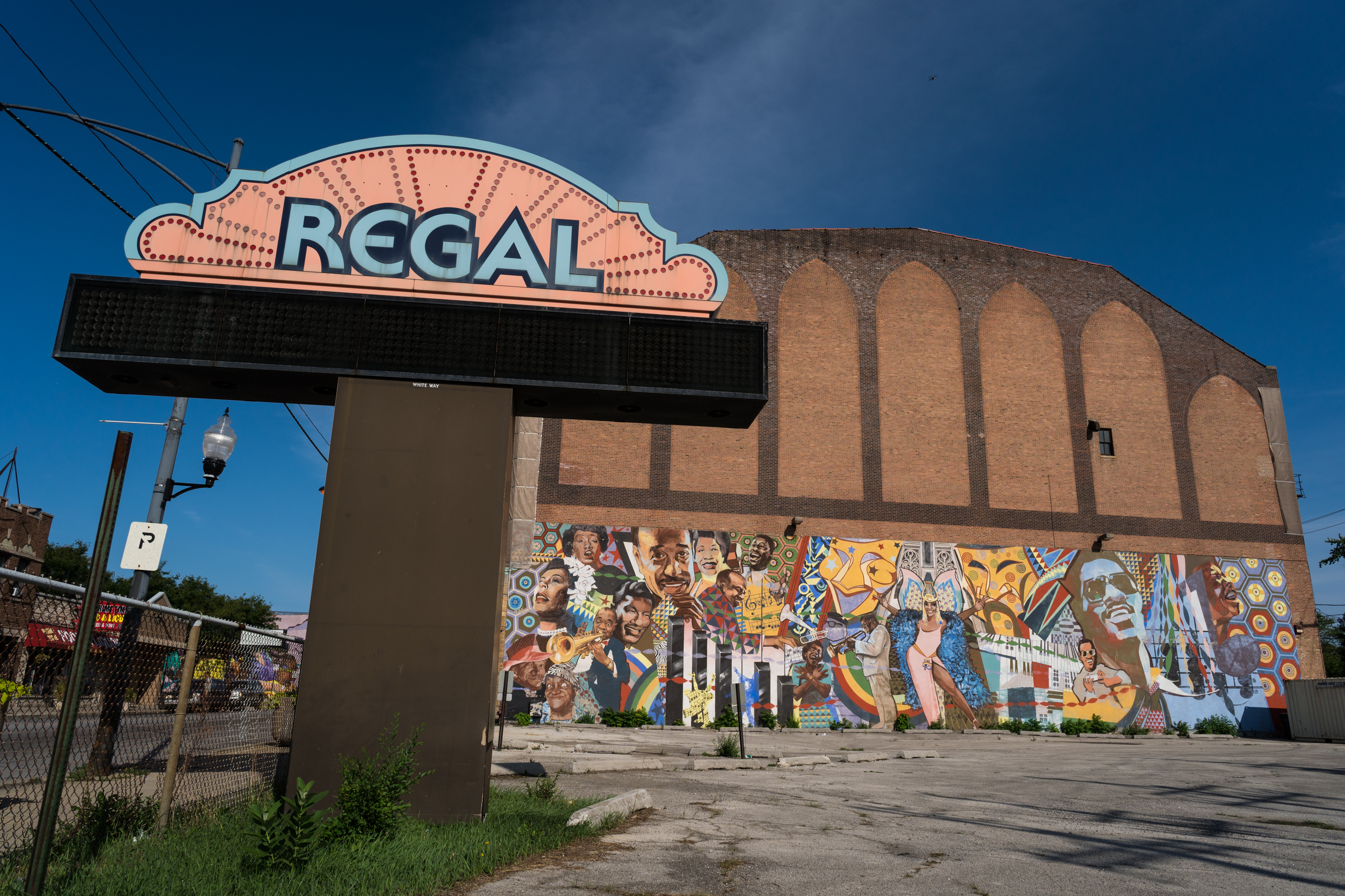 A mural outside the Avalon Regal Theater features musicians like Louis Armstrong.