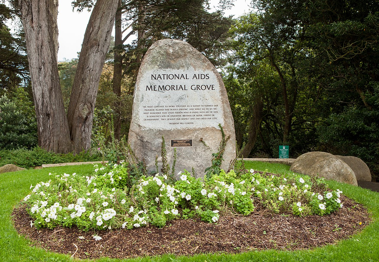 """A stone marker reading """"National AIDS Memorial Grove"""" in the middle of a field surrounded by trees."""