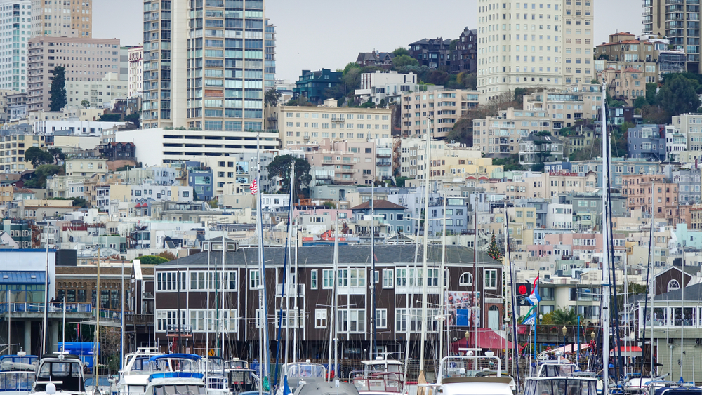 San Francisco homes on a hillside, with the masts of ships at the Marina in the foreground.