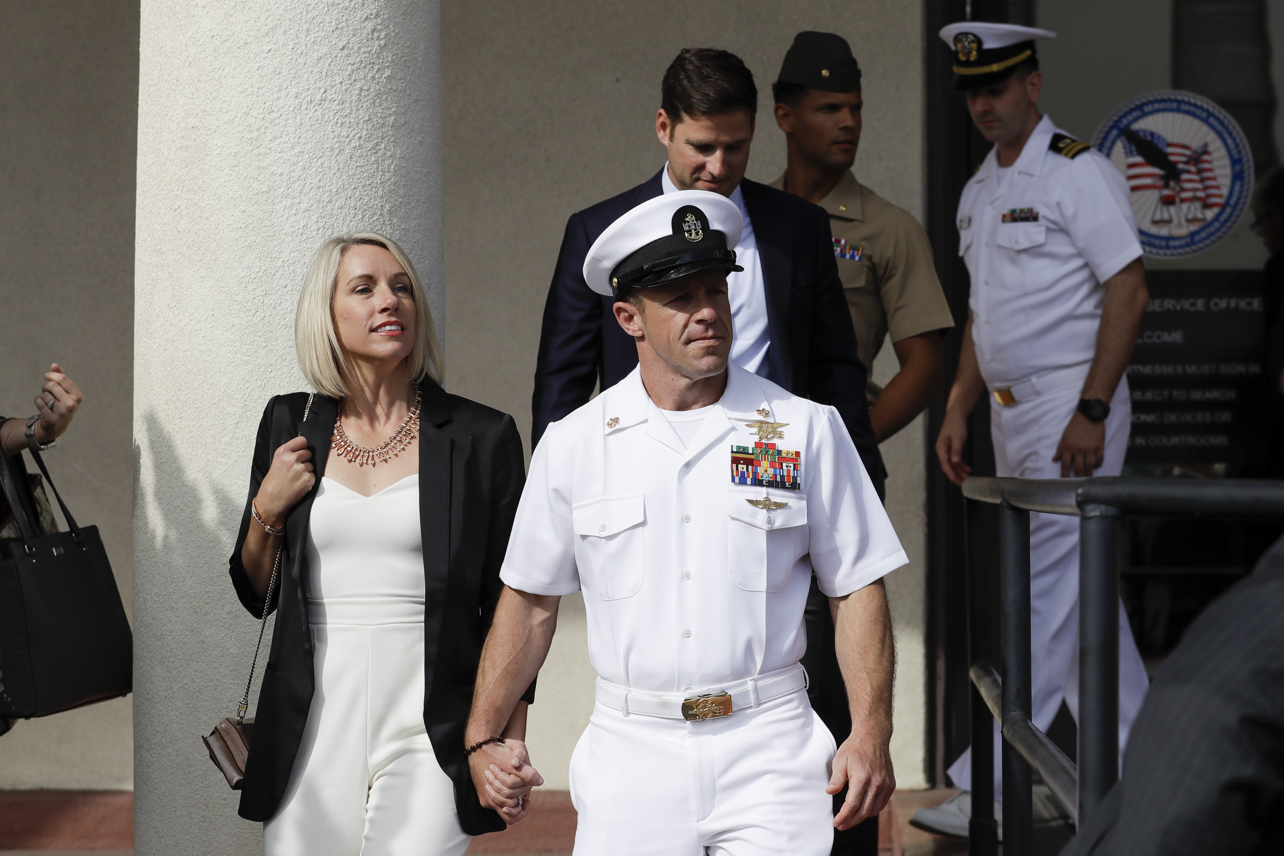 Navy Special Operations Chief Edward Gallagher, center, walks with his wife, Andrea Gallagher, as they leave a military court in San Diego in July.