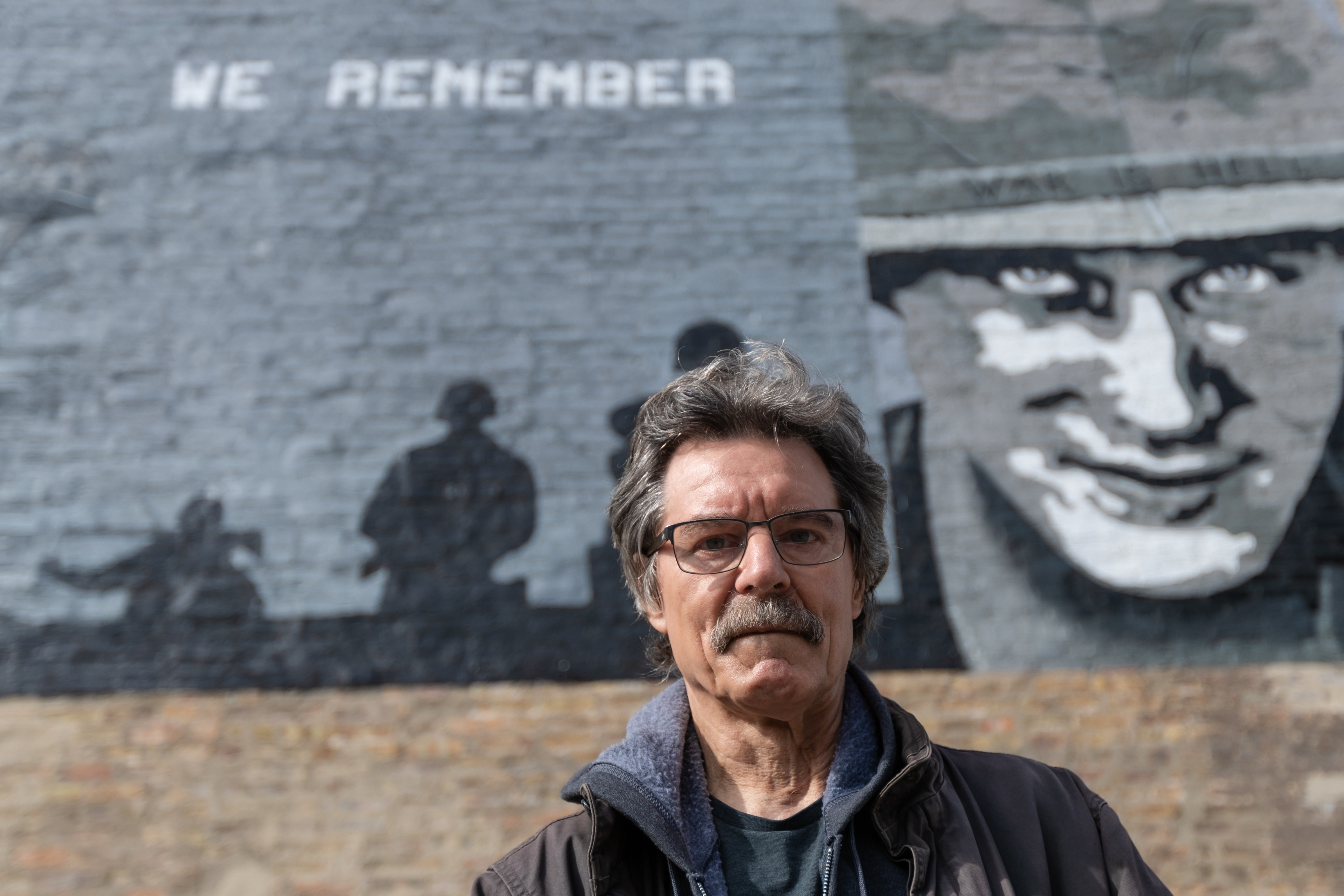 George Zaremba, who took up art late in life in part to better cope with having Parkinson's disease, stands in front of a mural he created to honor soldiers who served in Vietnam. The mural is on the corner of North Sacramento Boulevard and West Carroll Avenue.